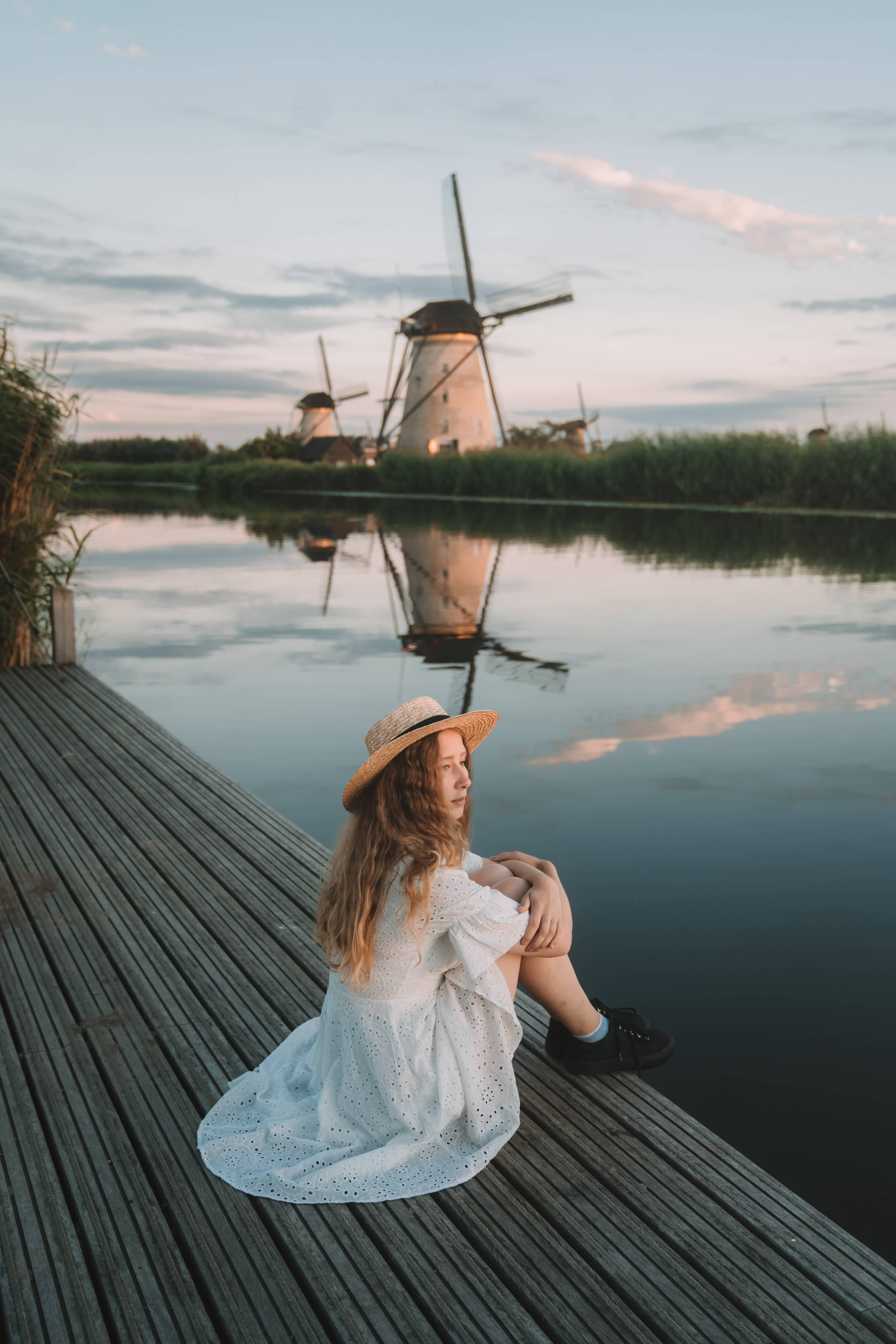 Girl in white dress wearing a hat sitting at the water in front of a windmill in Kinderdjik, Netherlands