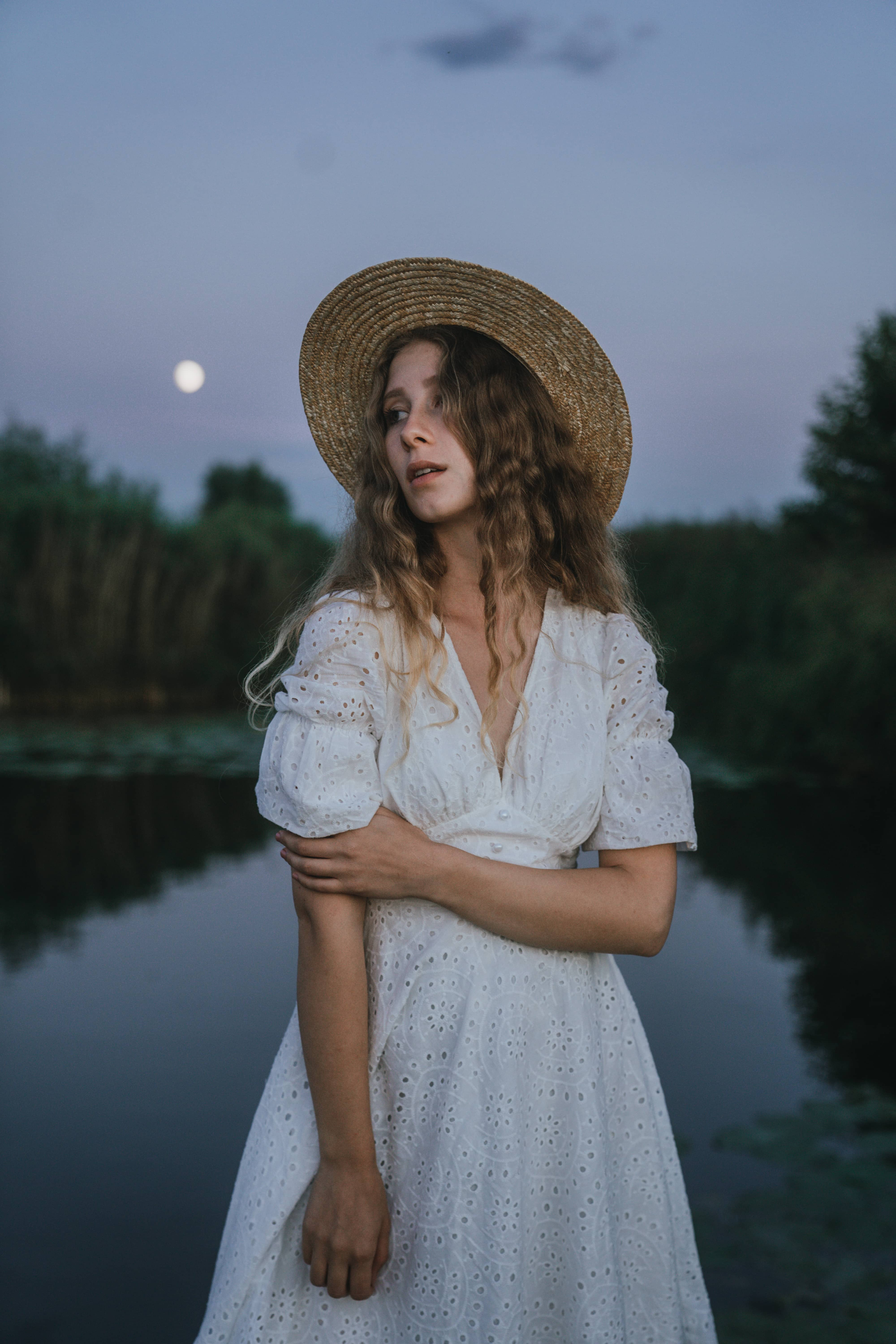Girl with fashionable white dress wearing a hat standing at the water in moonlight