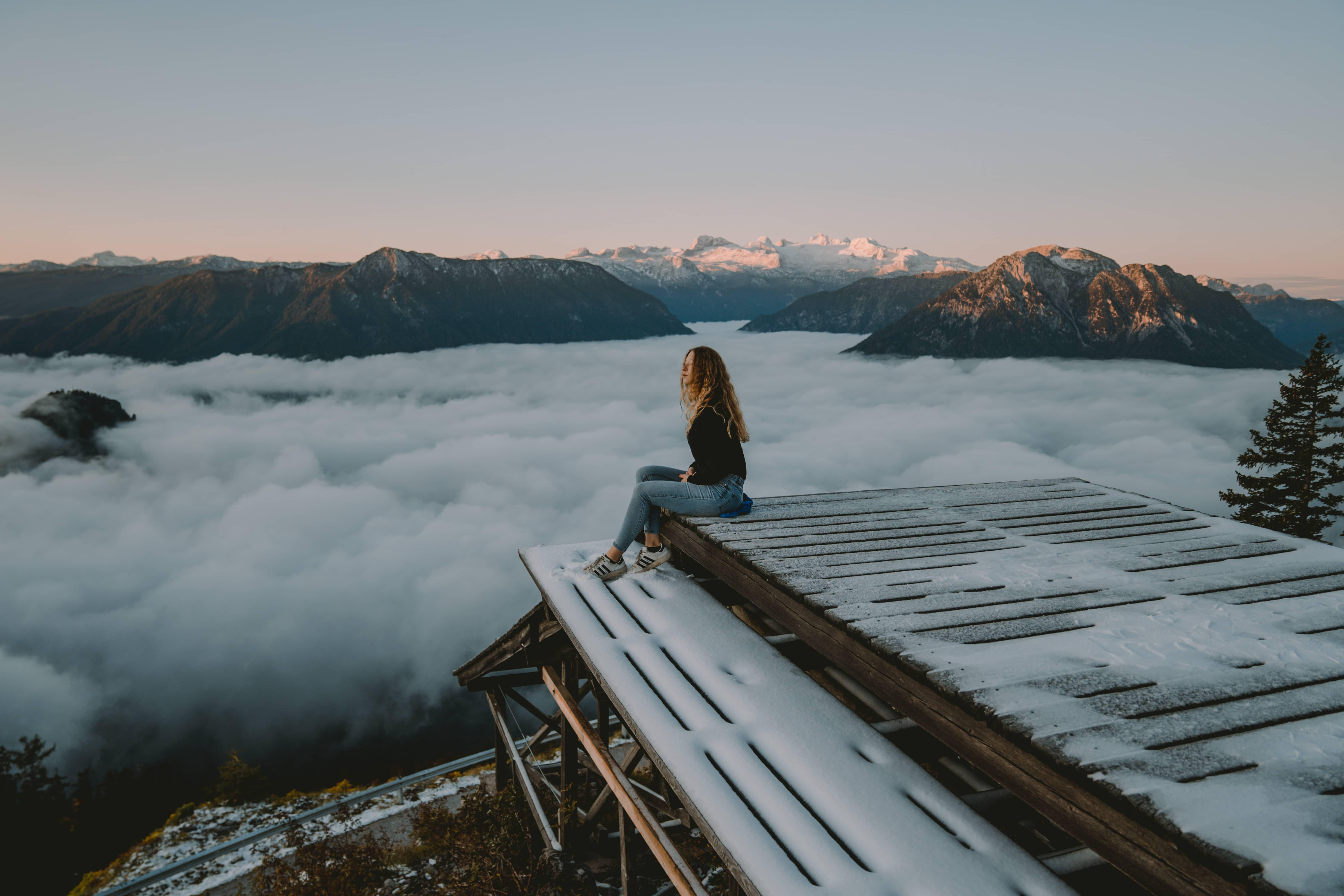 Girl sitting on a mountain watching the sunrise while a sea of clouds is spreading underneath her in the valley