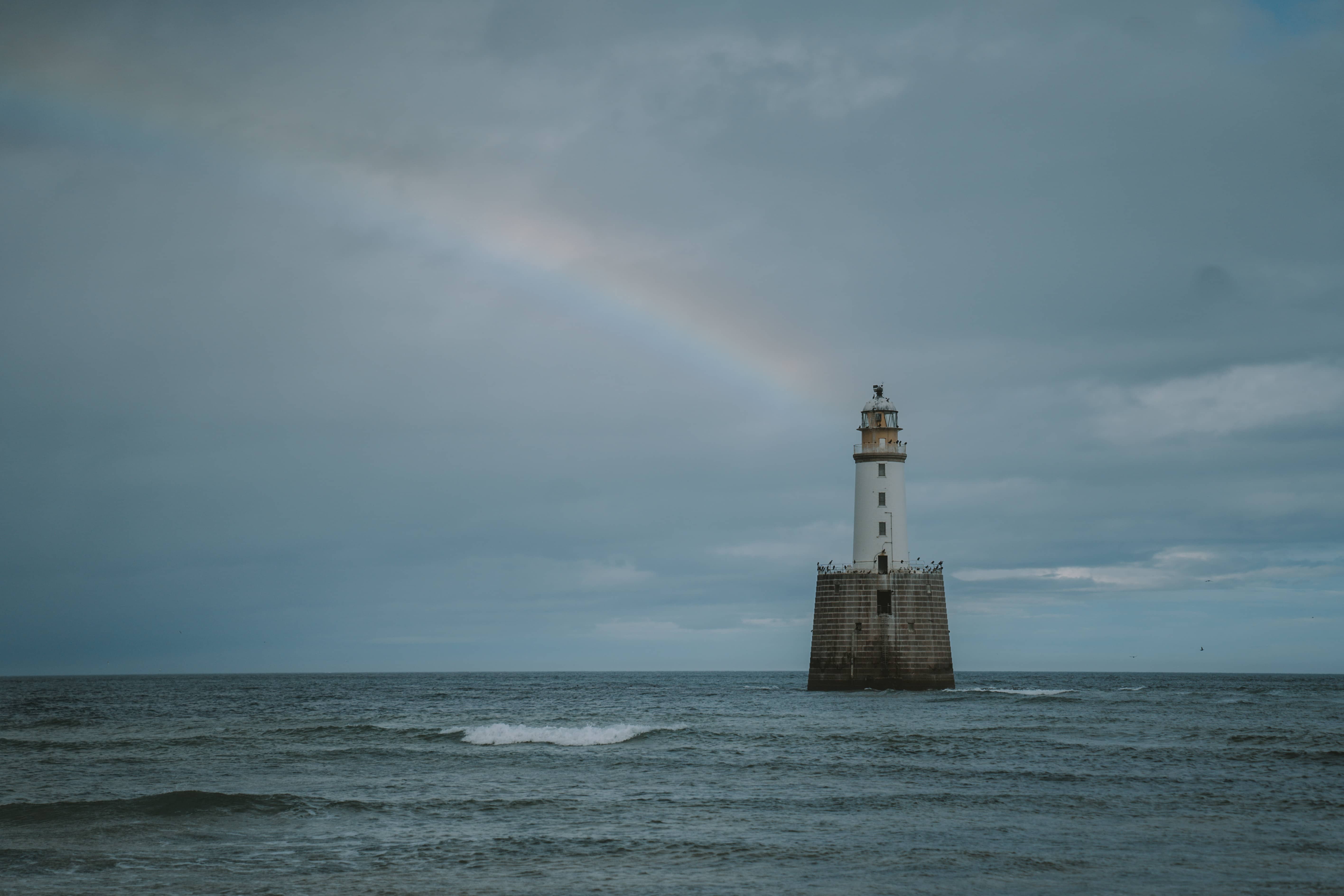 Rattray head light house in Scotland with a rainbow in the ocean