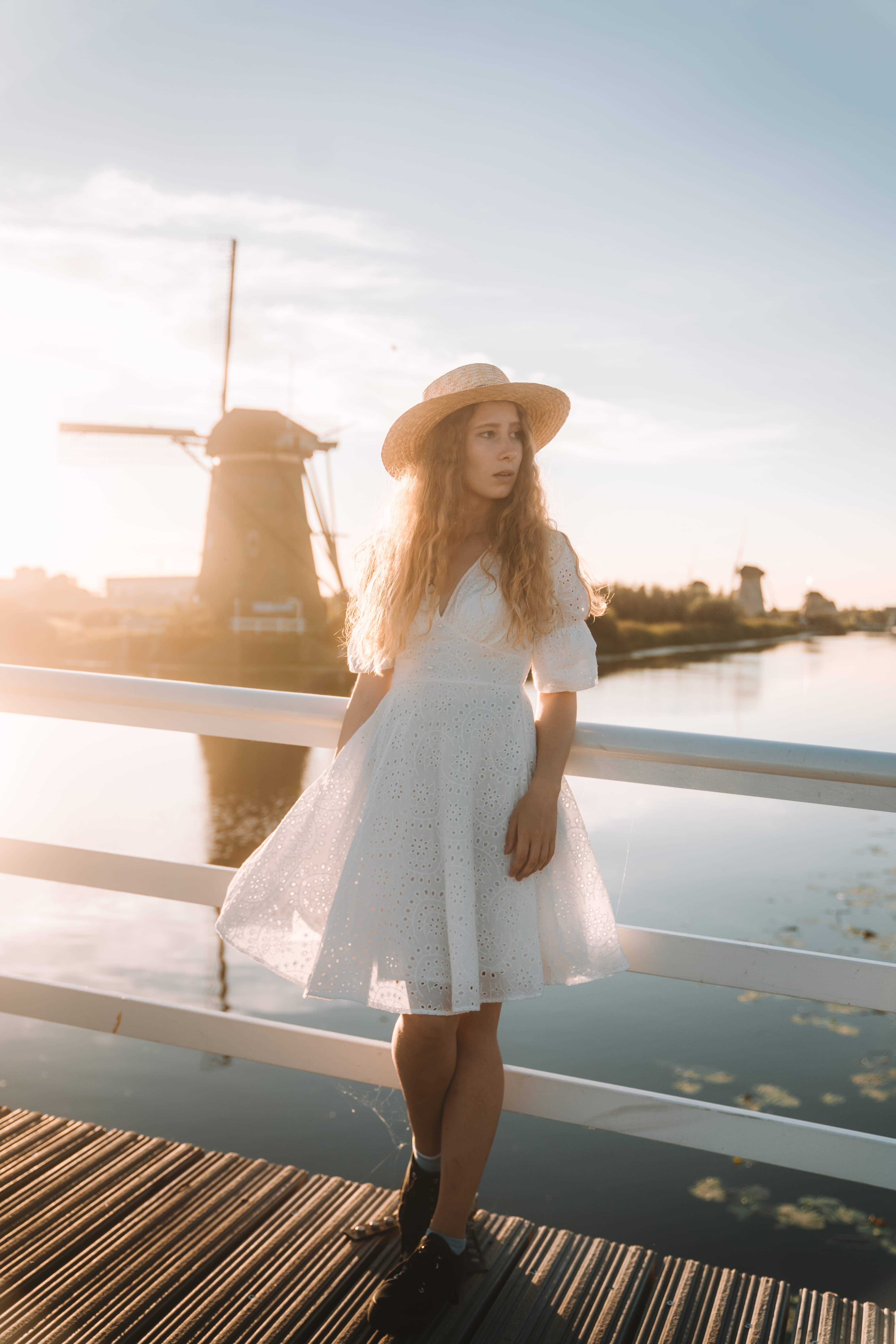 Girl in white dress wearing a hat standing in front of windmill while the sunset shines at her in golden light