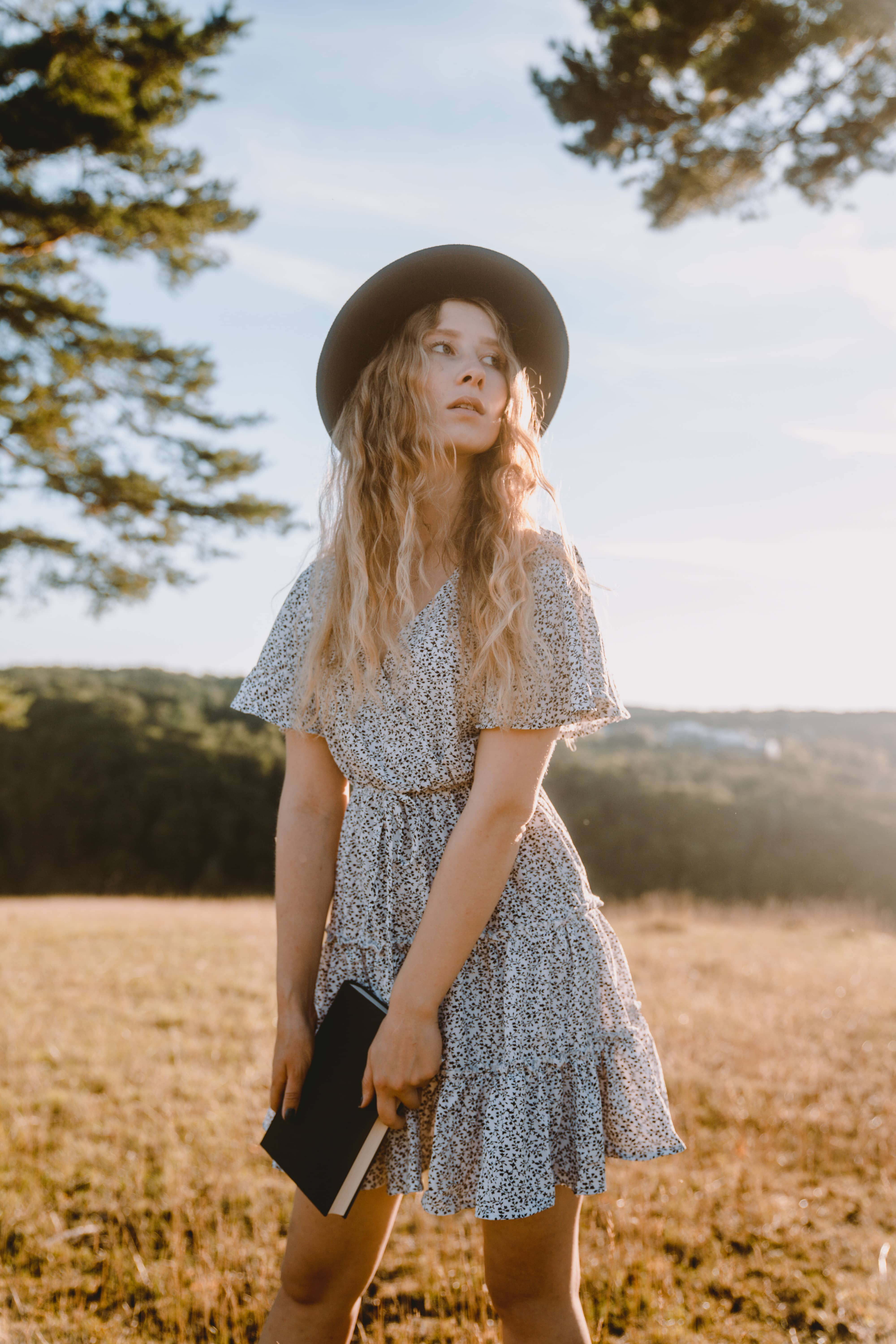Girl in white dress with black dots and a hat surrounded by nature has a book in her hands while sunset