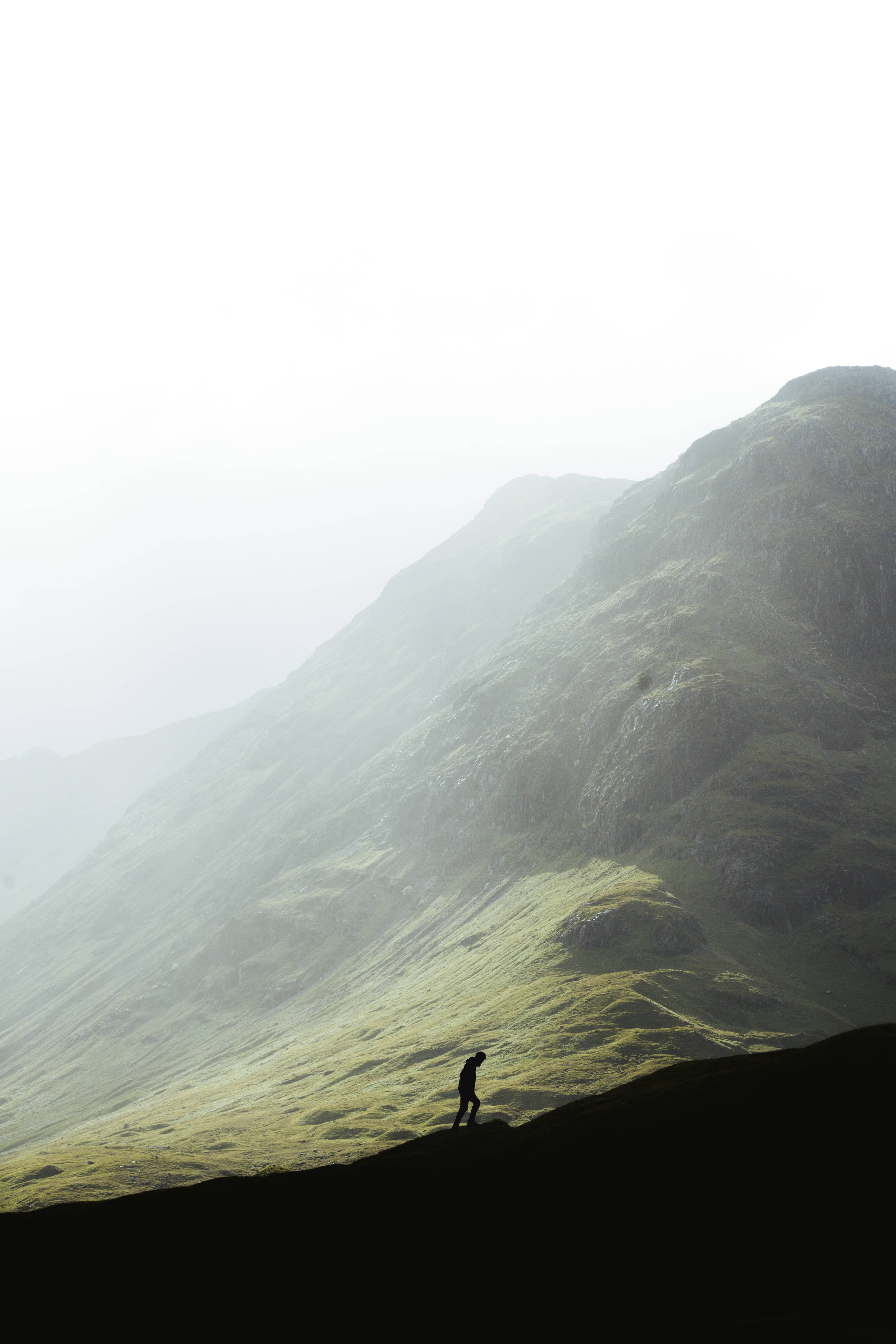 Silhouette of wanderer hiking up a hill in Scottish green highlands