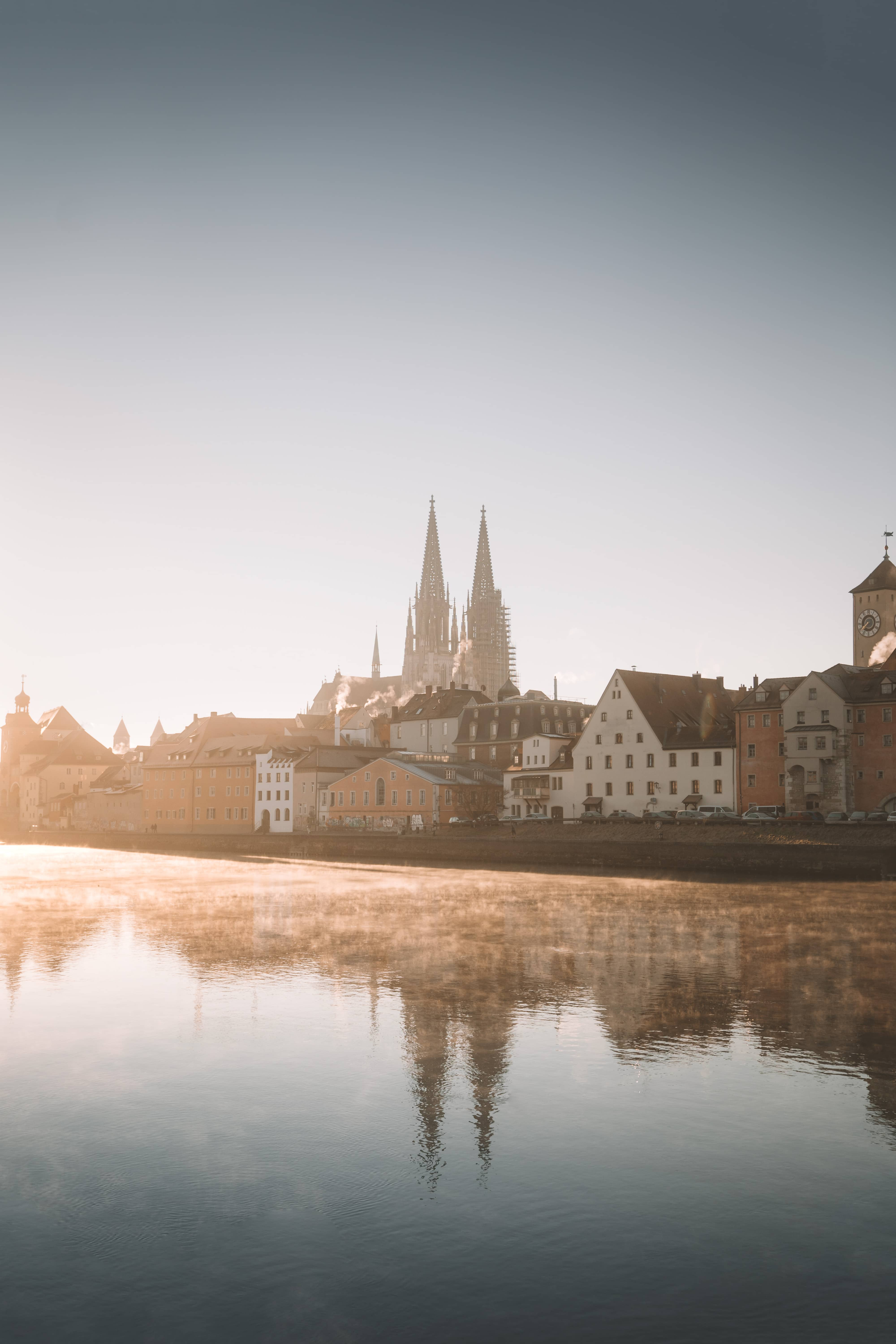 Regensburg cathedral reflecting in river Danube while sunrise
