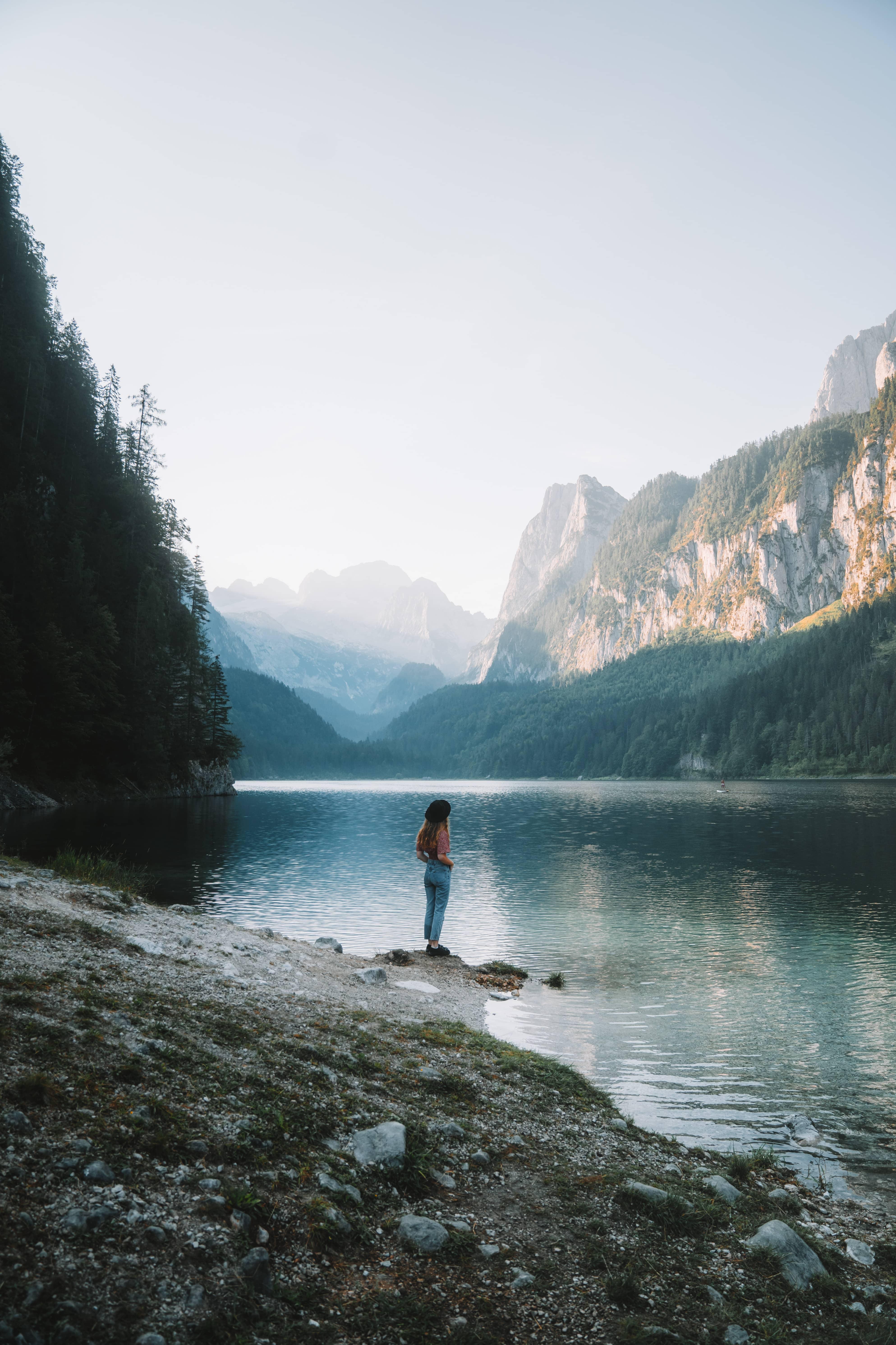 Girl standing at Lake Gosausee in Austria, Salzkammergut while sunrise. mountains reflecting in lake