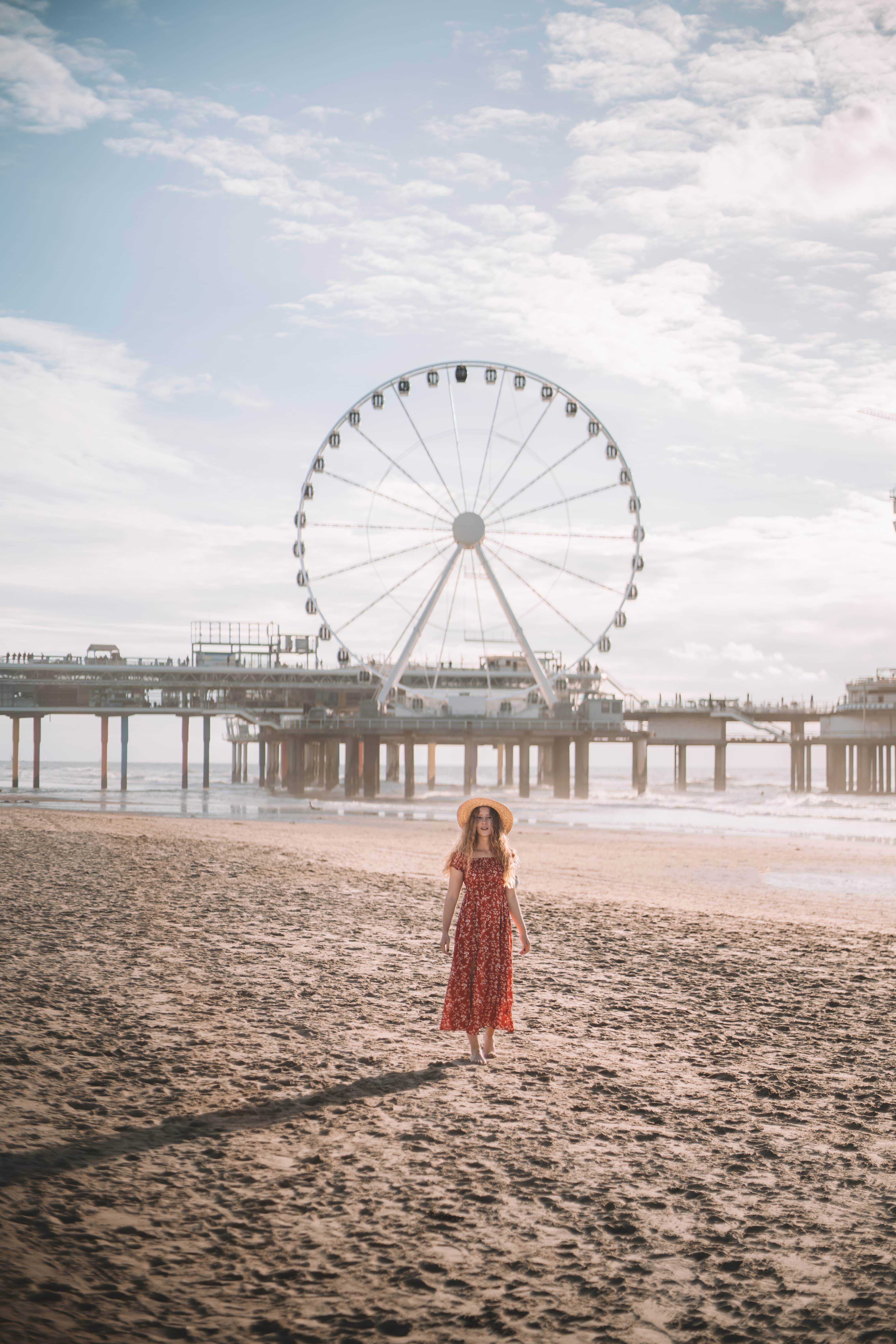 Girl in red dress standing at Scheveningen beach in Netherlands while sun is setting in the background
