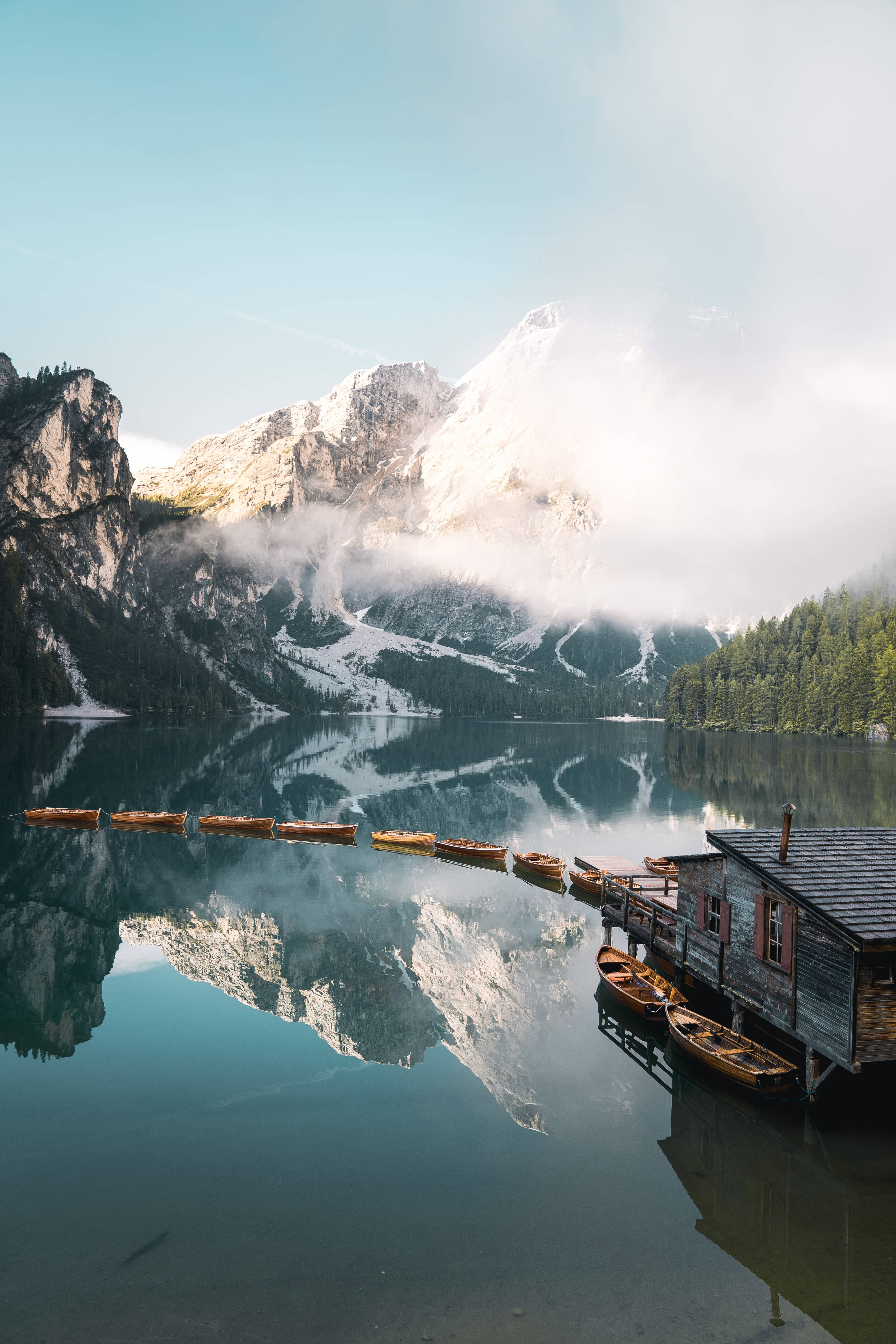 Lago di Braies, Pragser Wildsee in Italy while sunrise. Mountains shined on by sunrise reflecting in blue lake with boat house