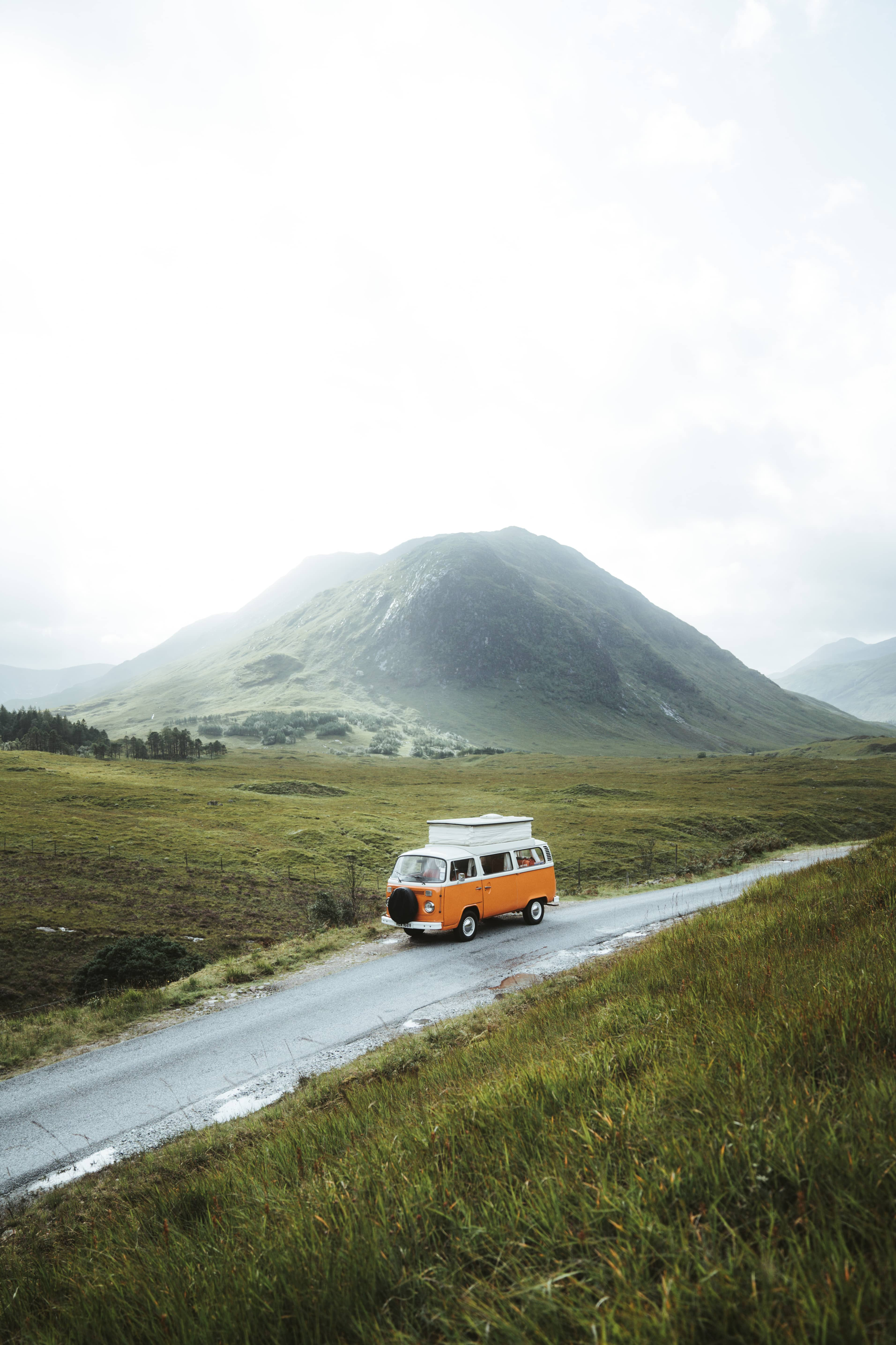 Volkswagen T2 with pop-up roof standing in front of Scottish highlands besides road Glenn Etive