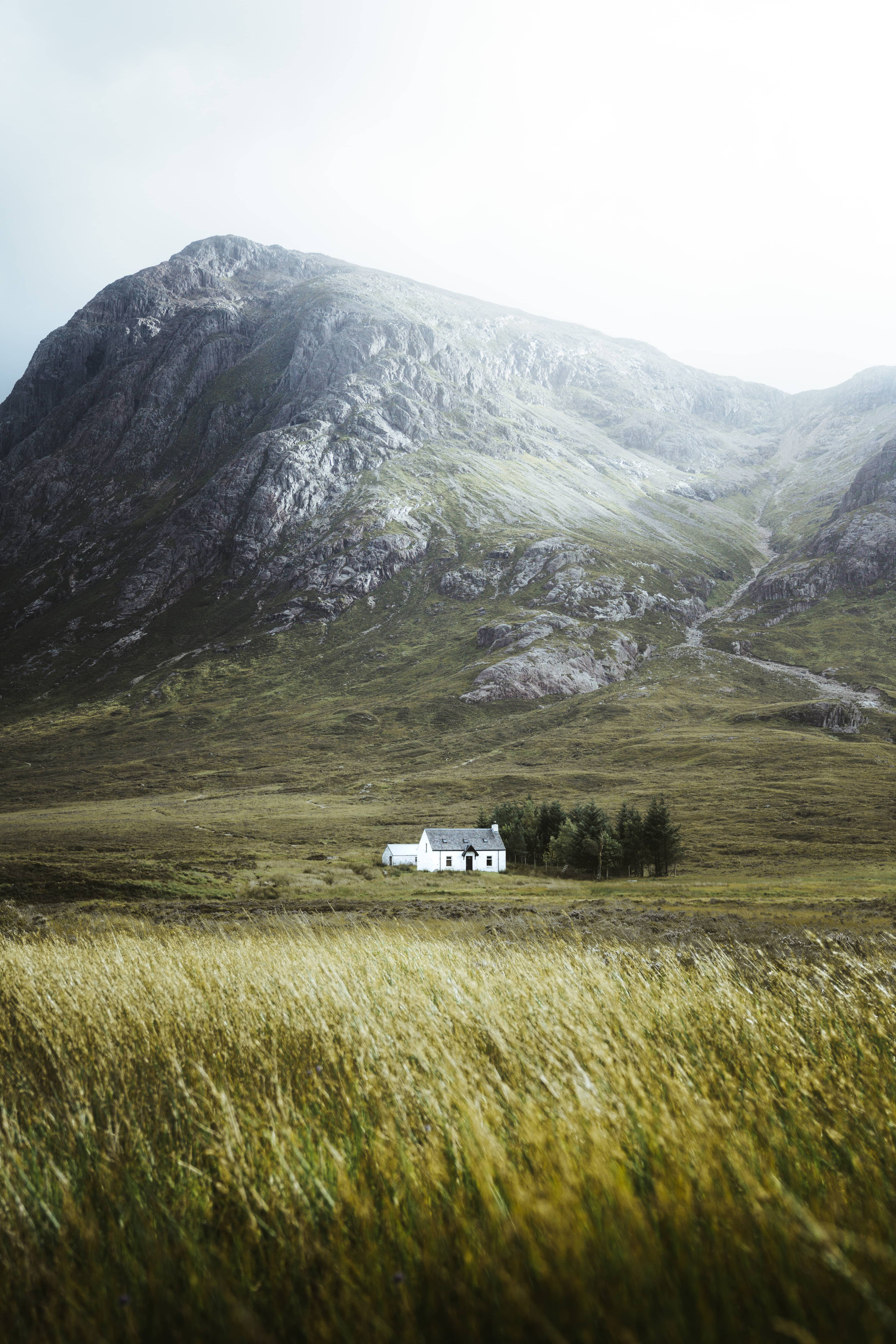 small cottage in glen coe very remotely in front of big Scottish highland mountains