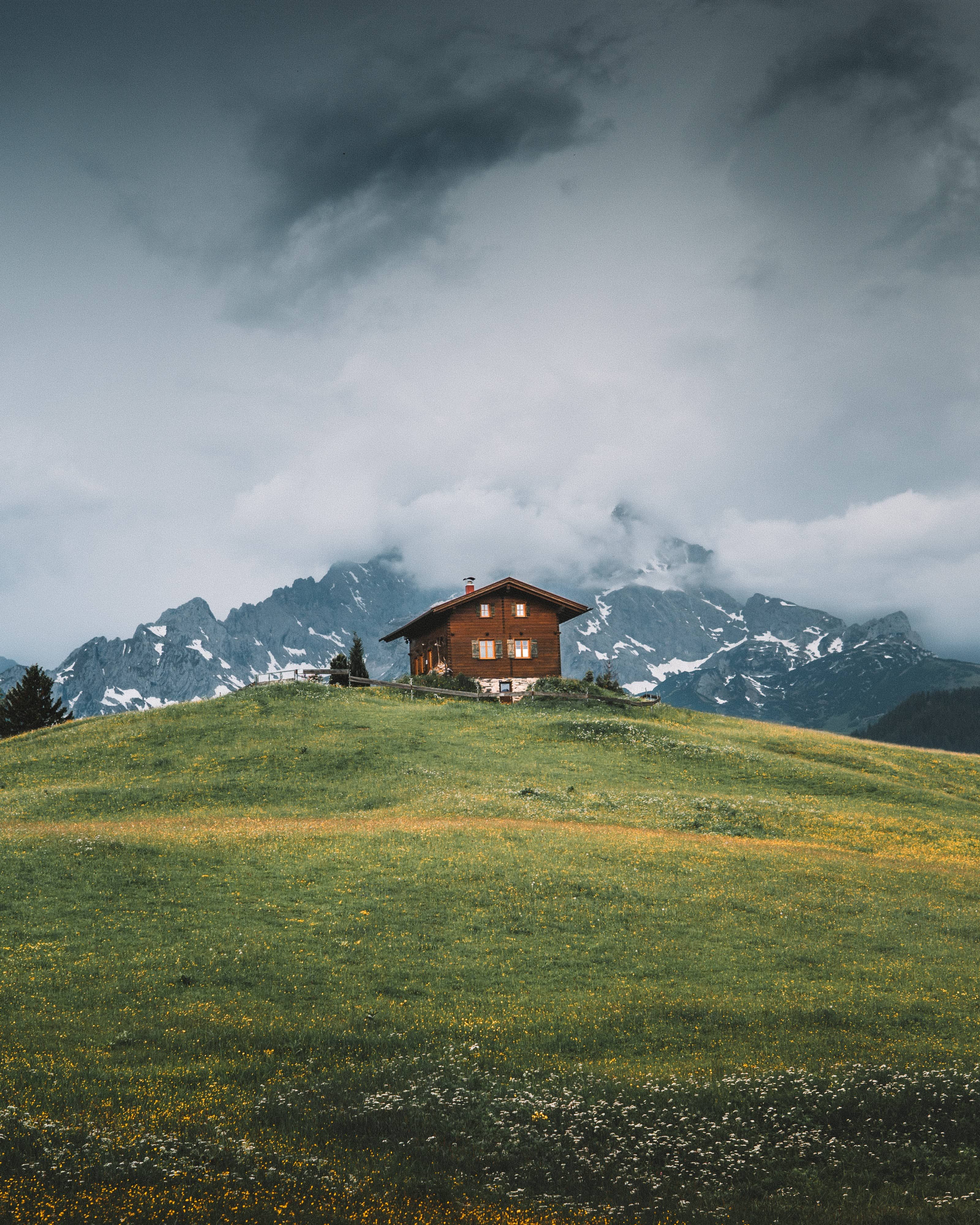 Mountain hut build on a big grass hill in front of big mountains while dark clouds in the sky