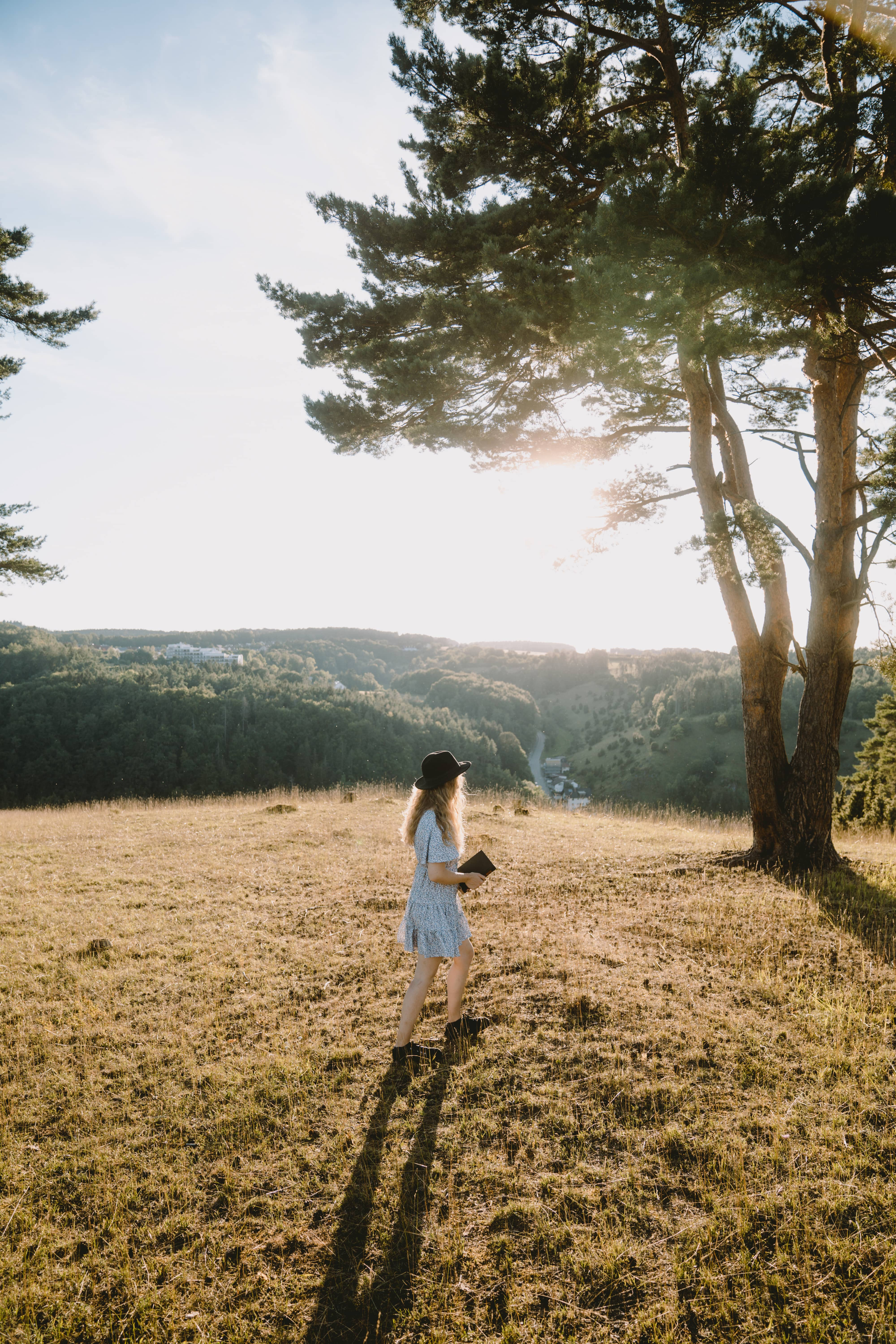 Girl in white dress wearing a hat walking towards tree while sun sets behind her