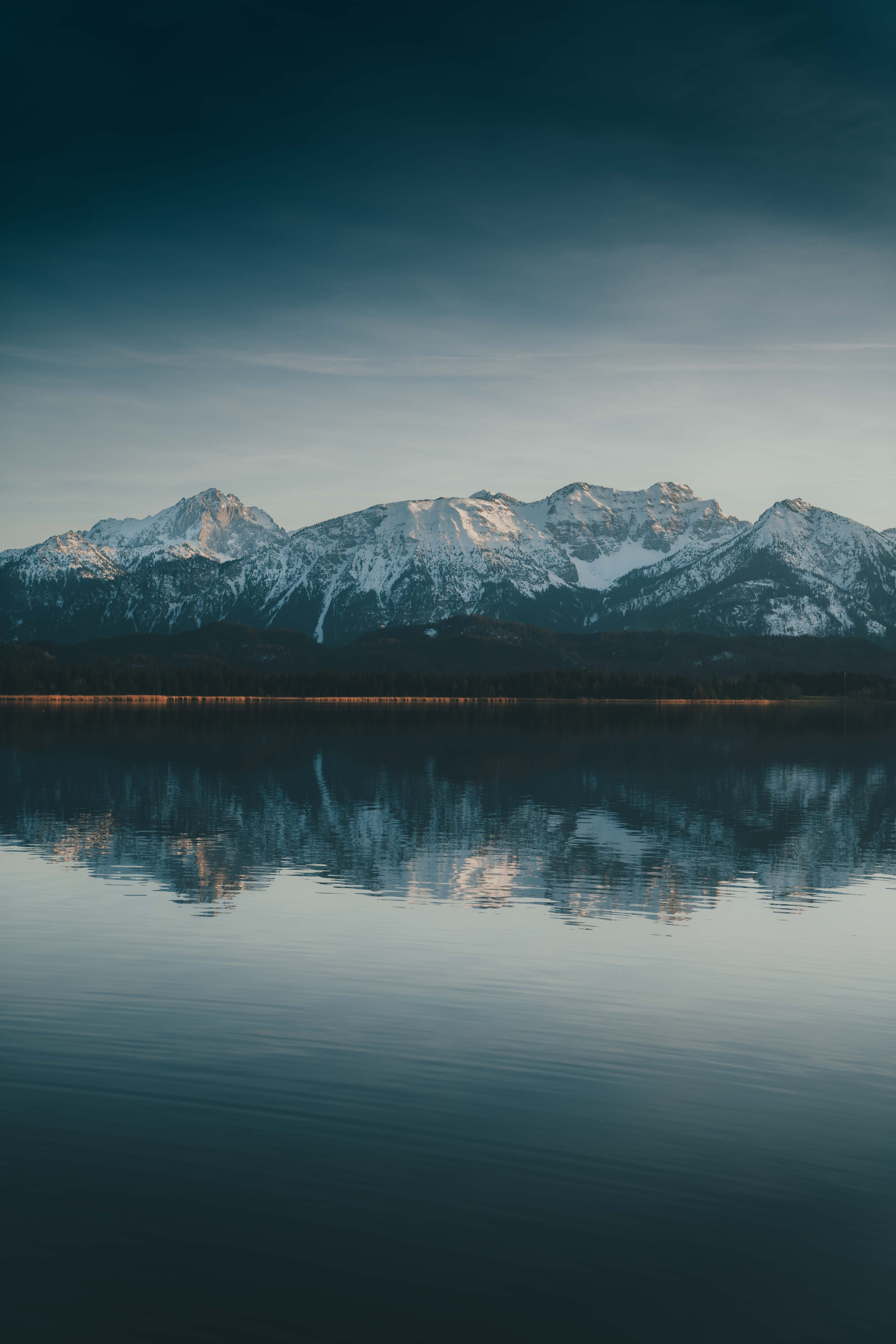 Dark reflection of Mountains in lake Hopfensee in Bavaria, Germany
