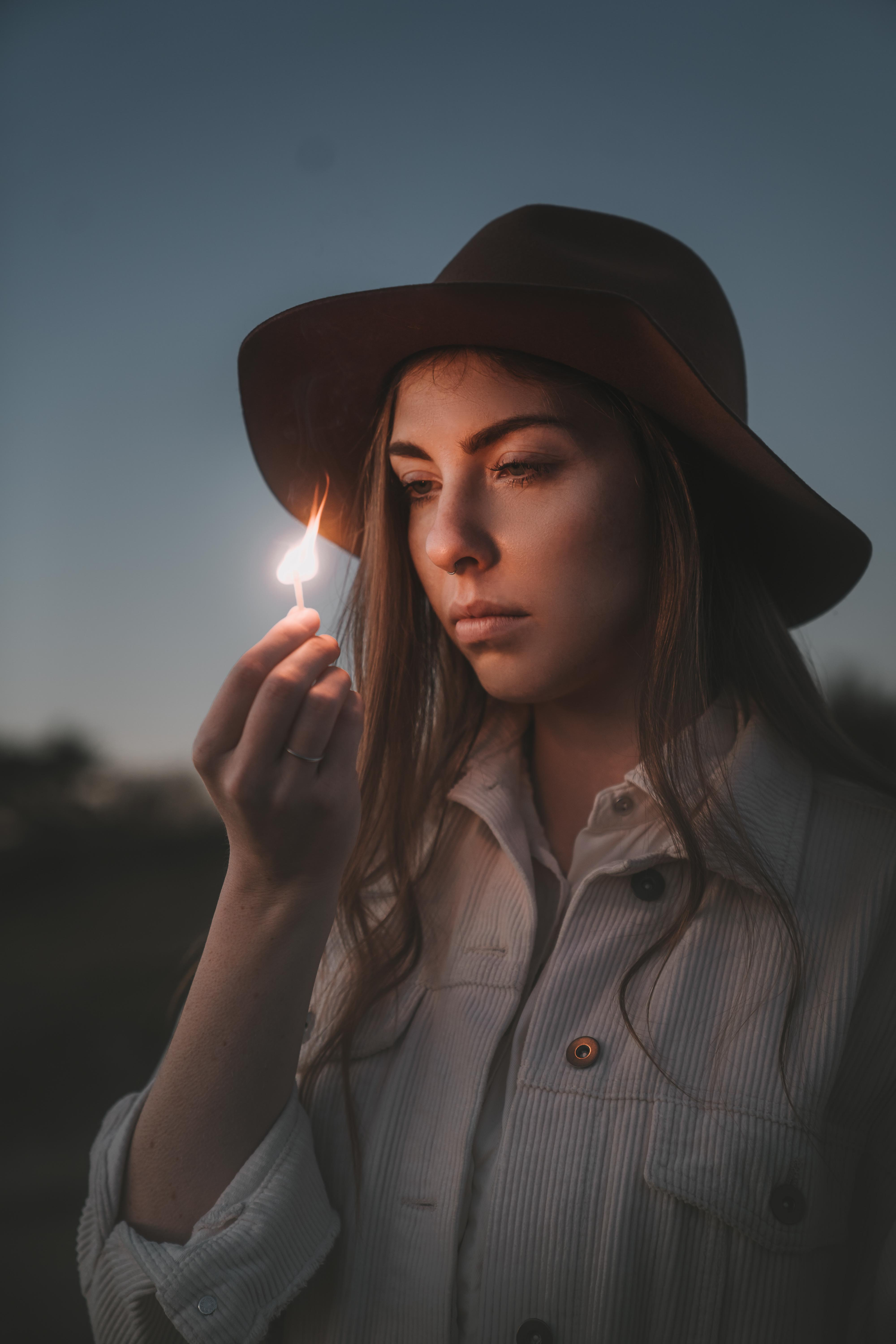 Woman with hat looking into a burning match while it is dark outside