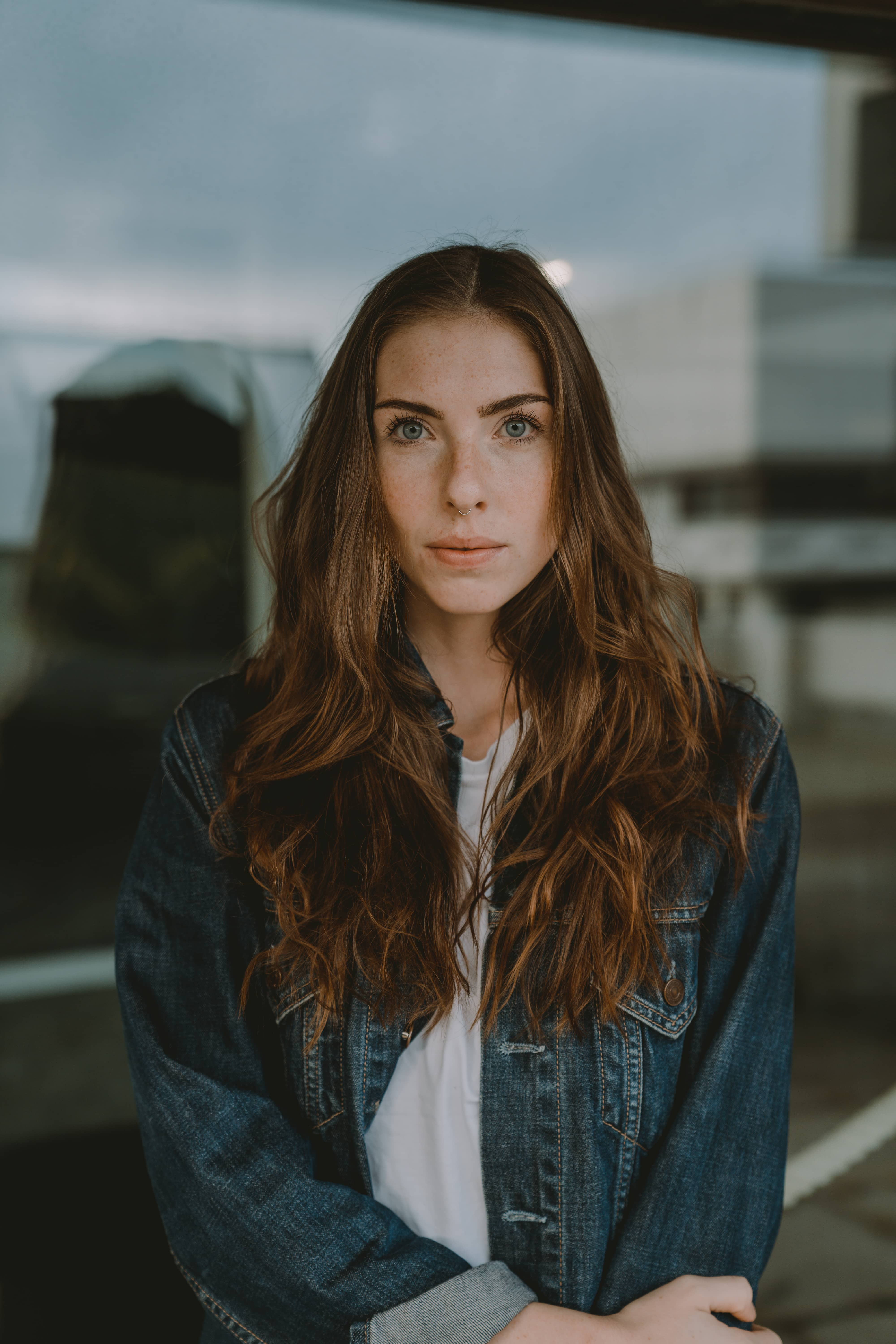 women with brown hair wearing a jeans jacket standing in front of glass
