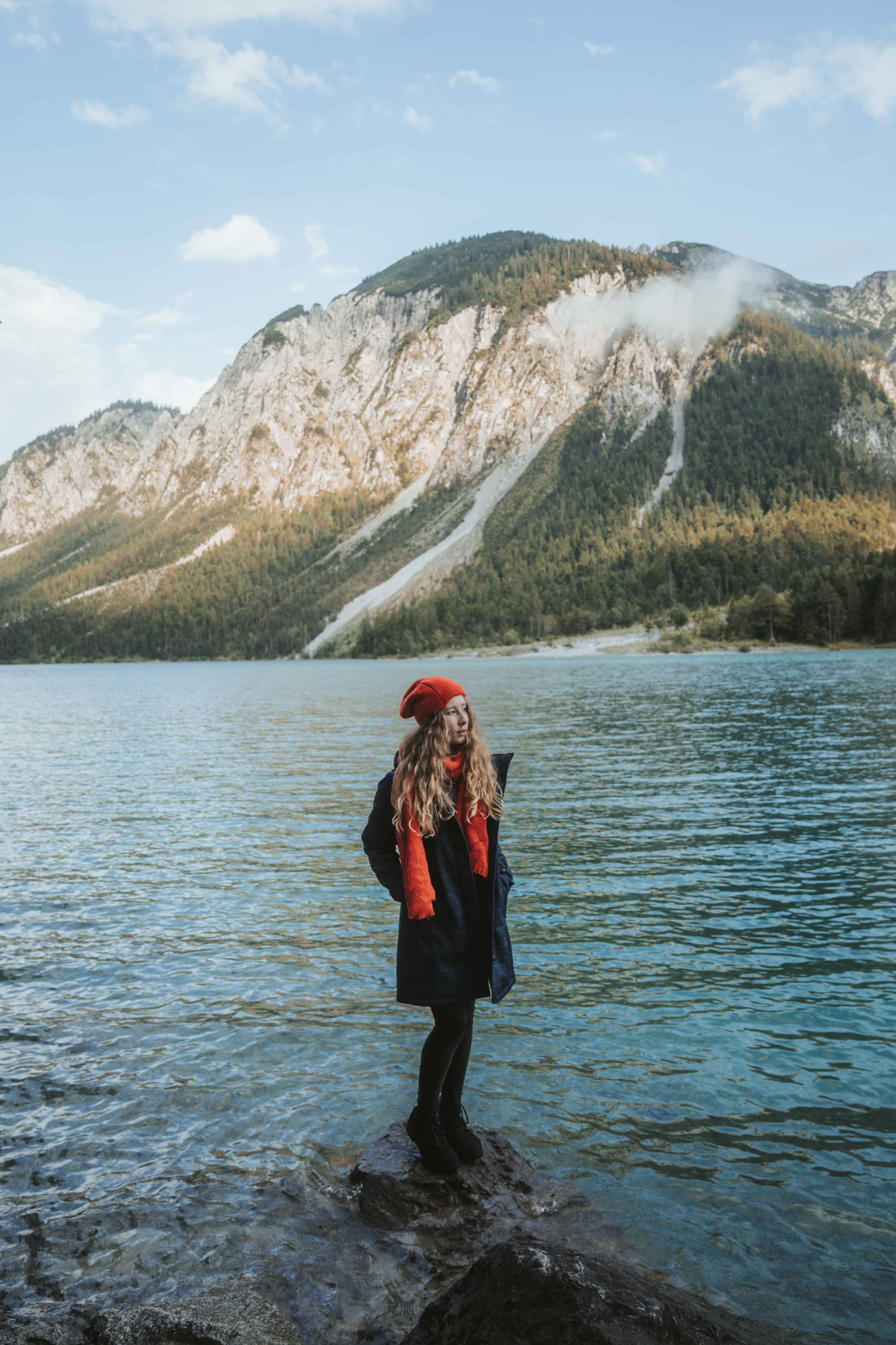 women wearing red Elkline scarf and cap standing at lake Plansee in Austria