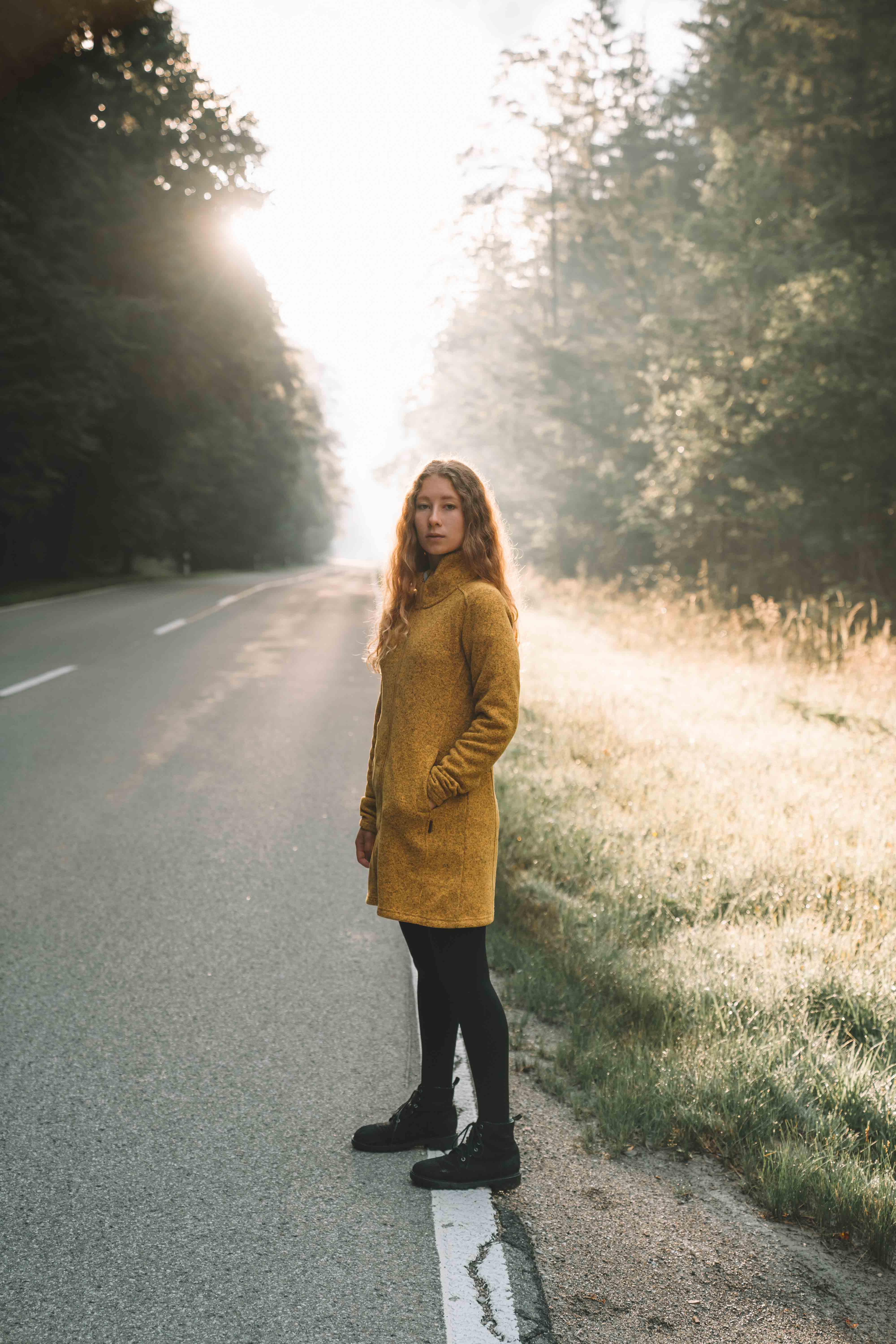 women wearing yellow elkline jacket standing besides a road while the sun rises behind her
