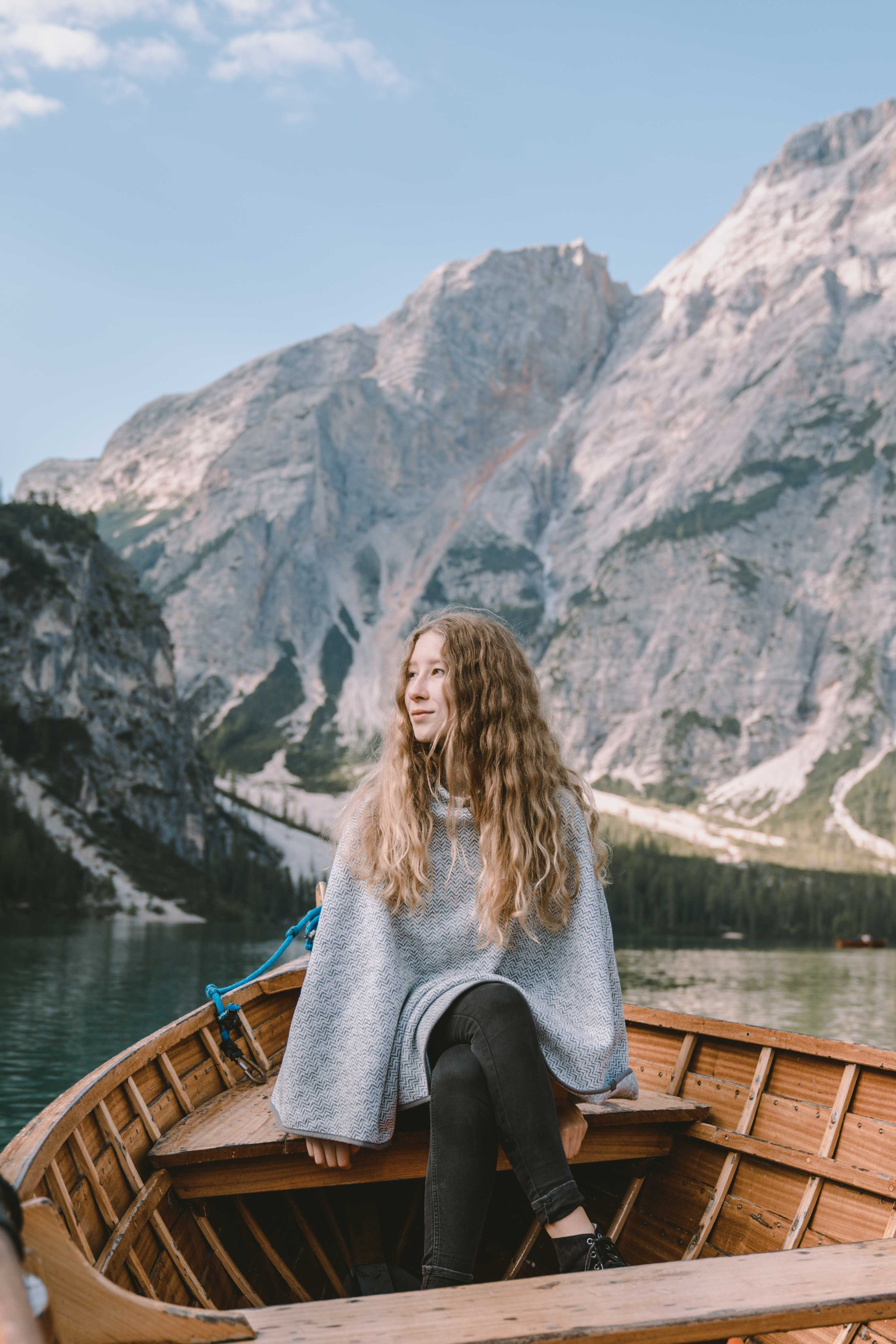 Women wearing a grey poncho by Elkline sitting in a boat on a mountain lake in Italy