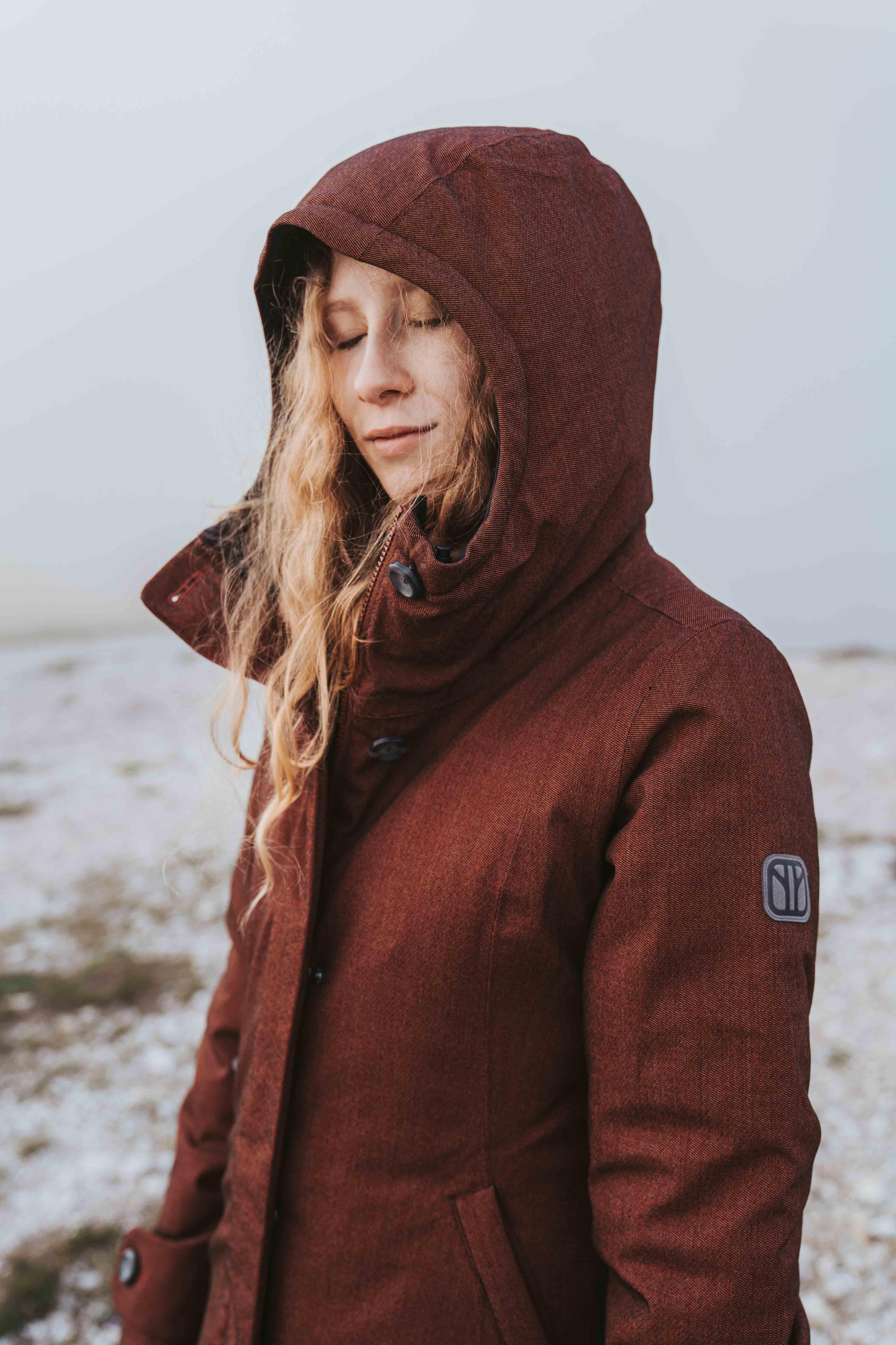 Women wearing red winter jacket by Elkline smiling
