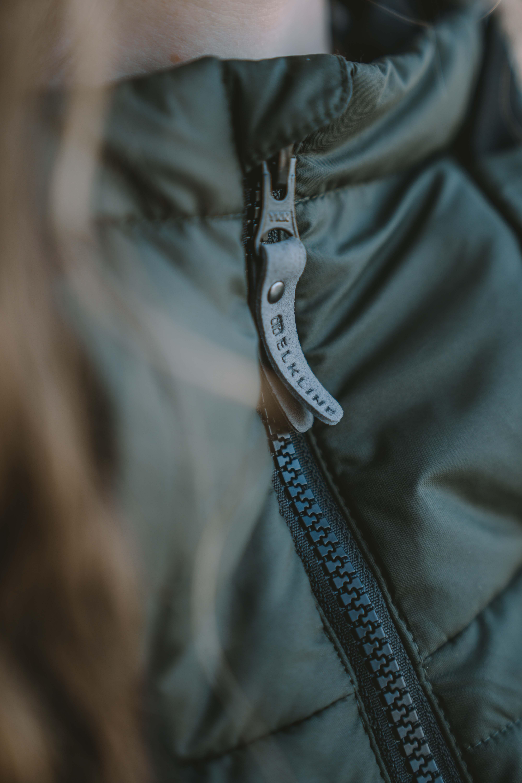 close up photograph of zipper of green jacket by Elkline