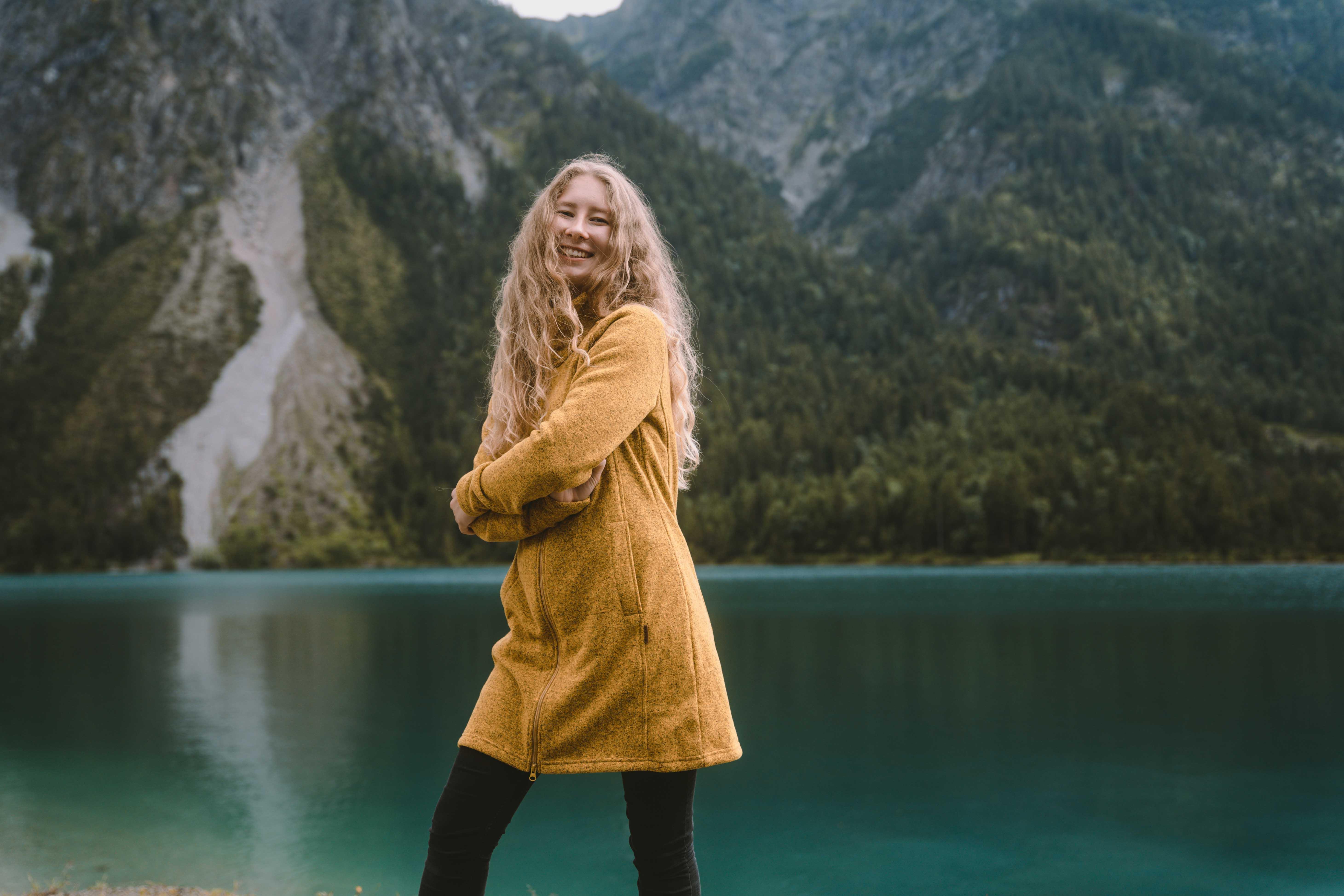 Women smiling wearing yellow jacket by Elkline standing in front of mountain lake