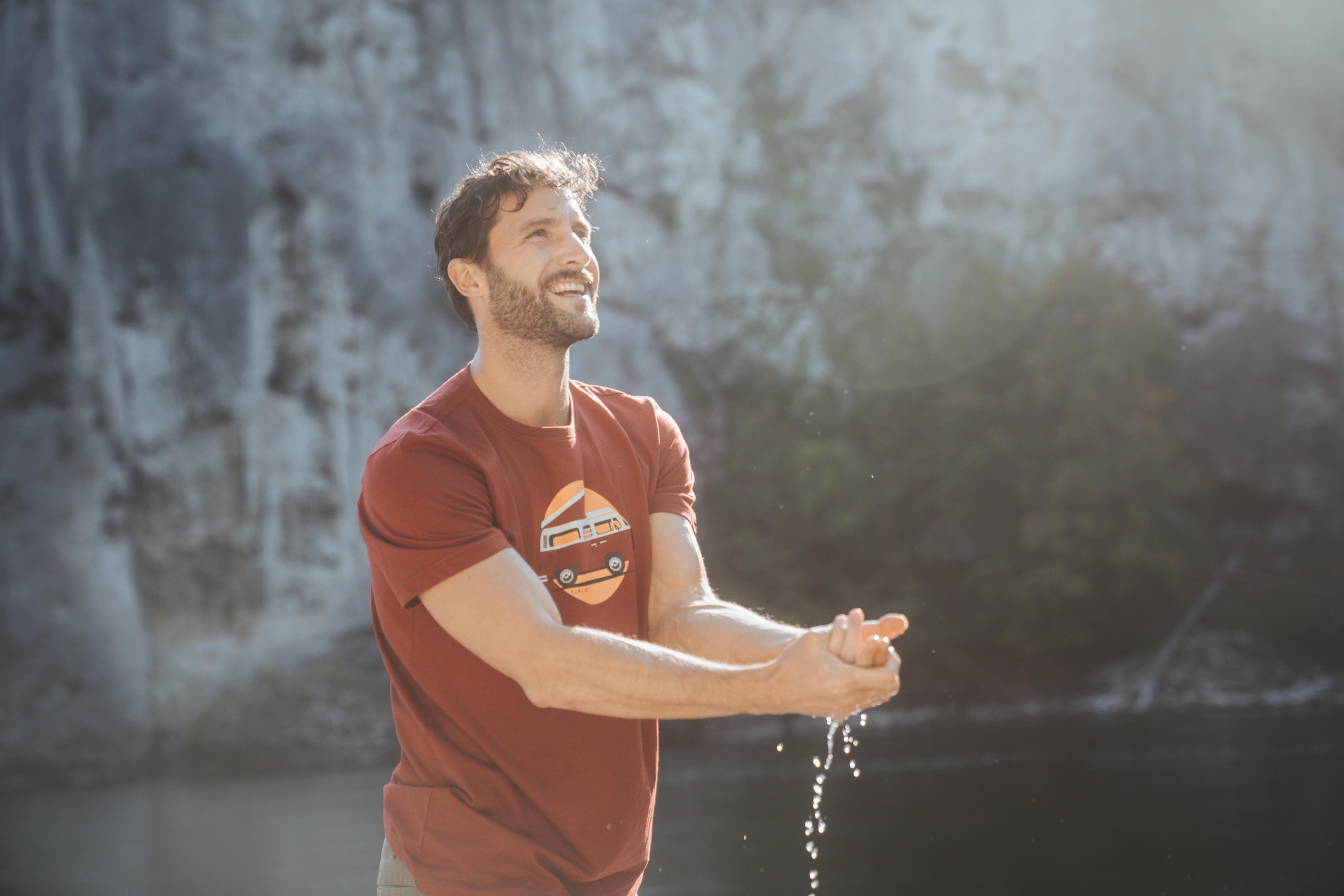 middle aged man with beard wearing red shirt by Elkline standing in sunlight while washing his hands with water