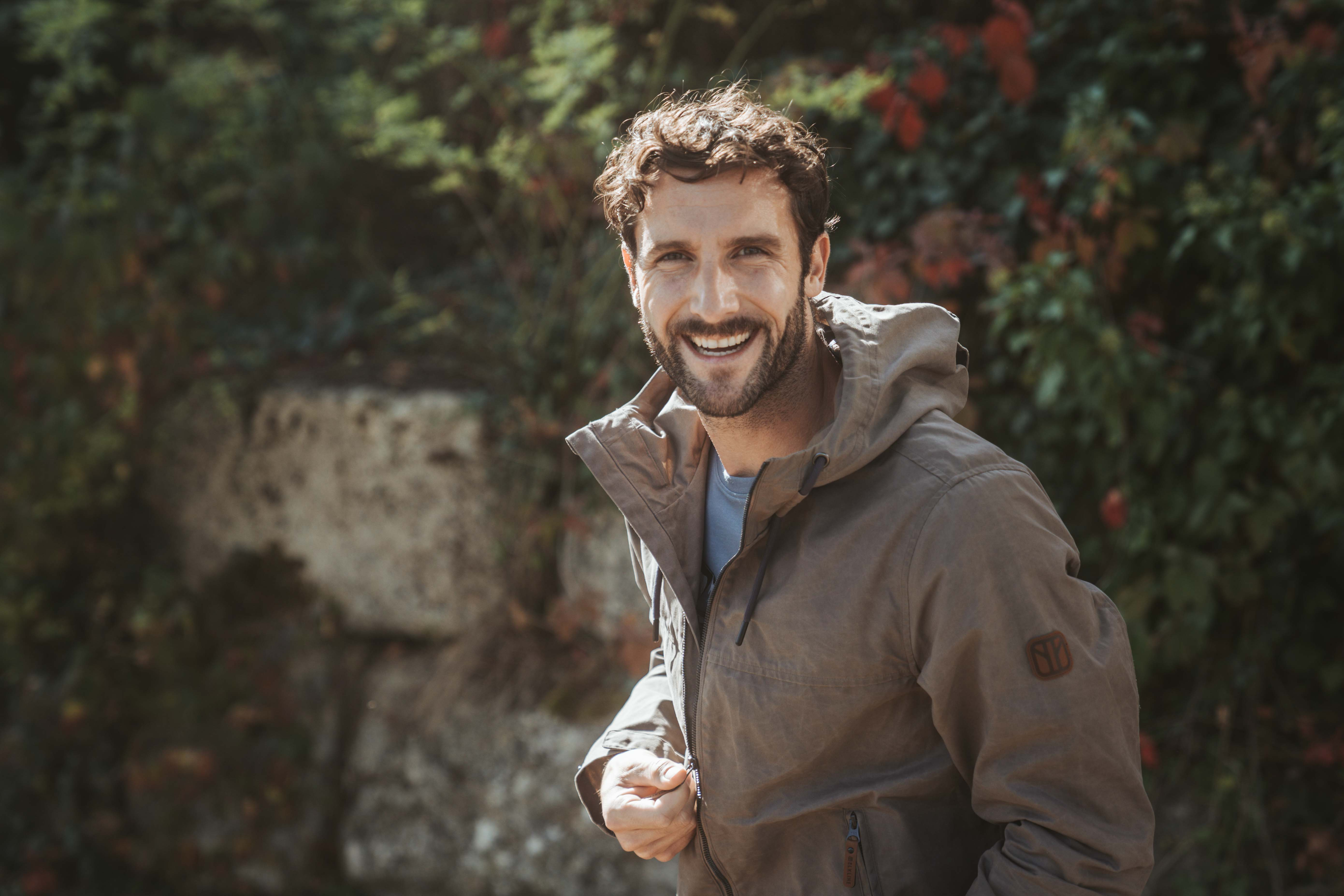 Middle aged man with beard standing in sunlight smiling wearing a brown jacket by Elkline