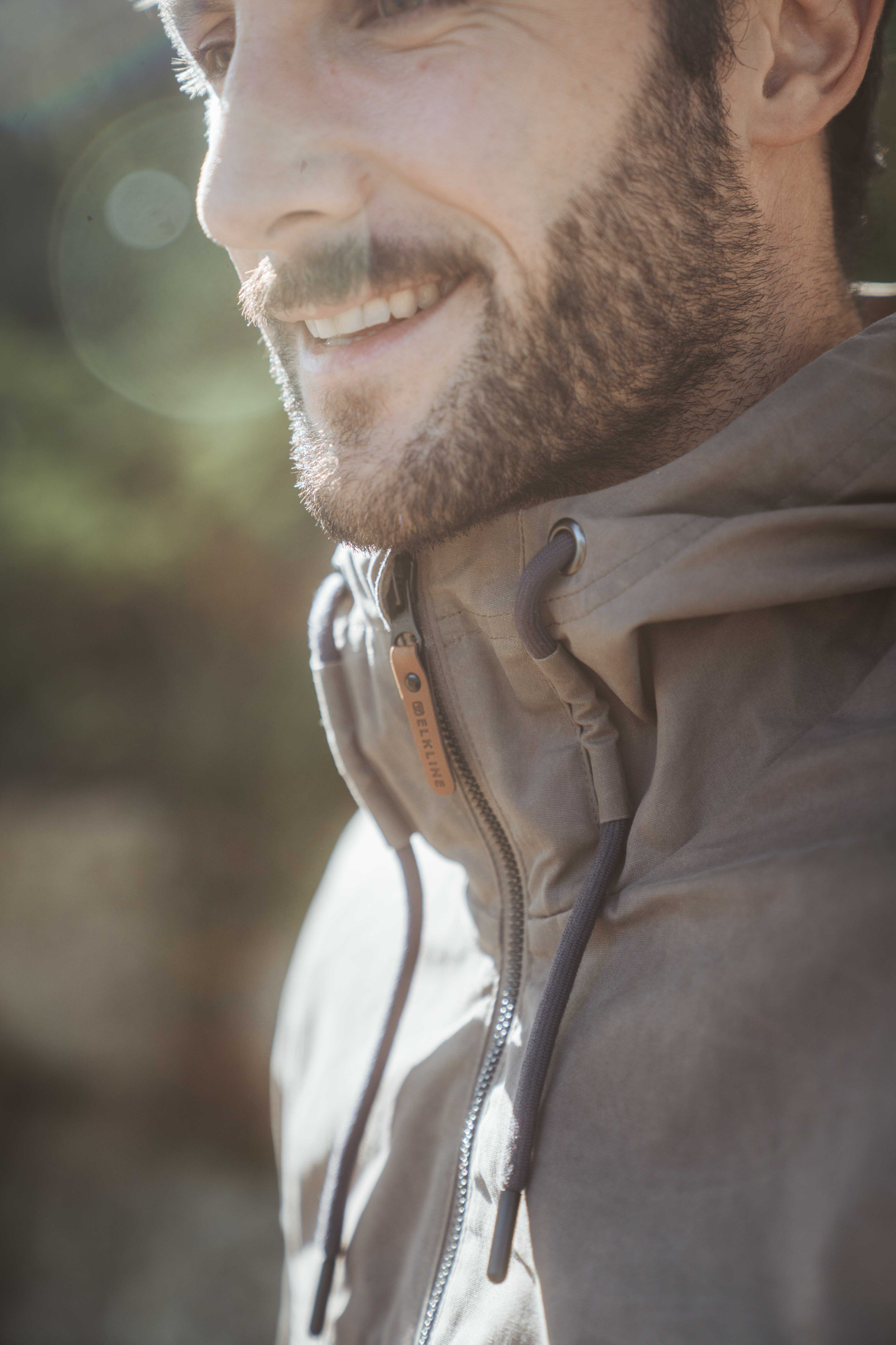 Man with beard smiling wearing a brown jacket by Elkline