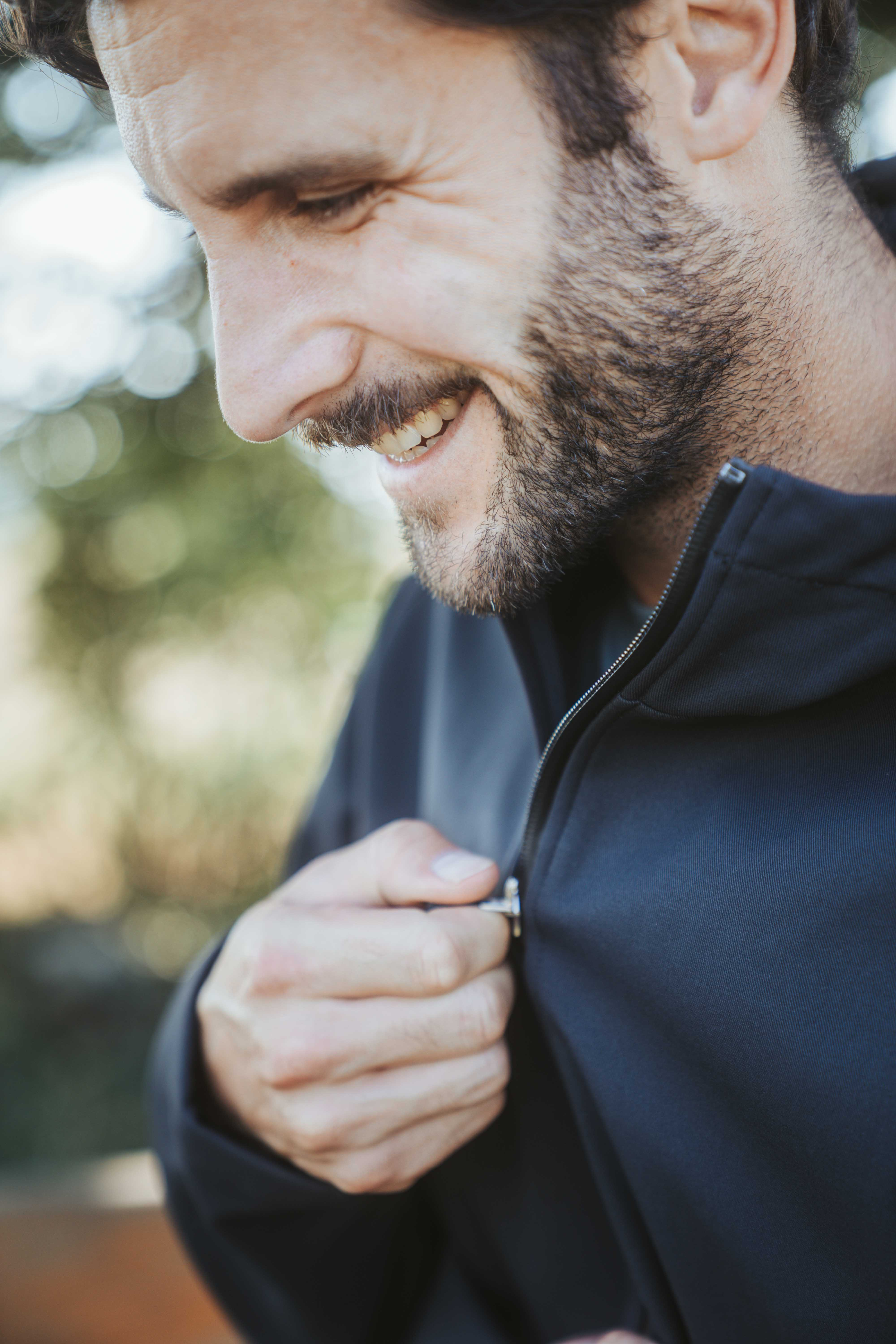 man with beard laughing while pulling up zipper of his jacket made by Elkline