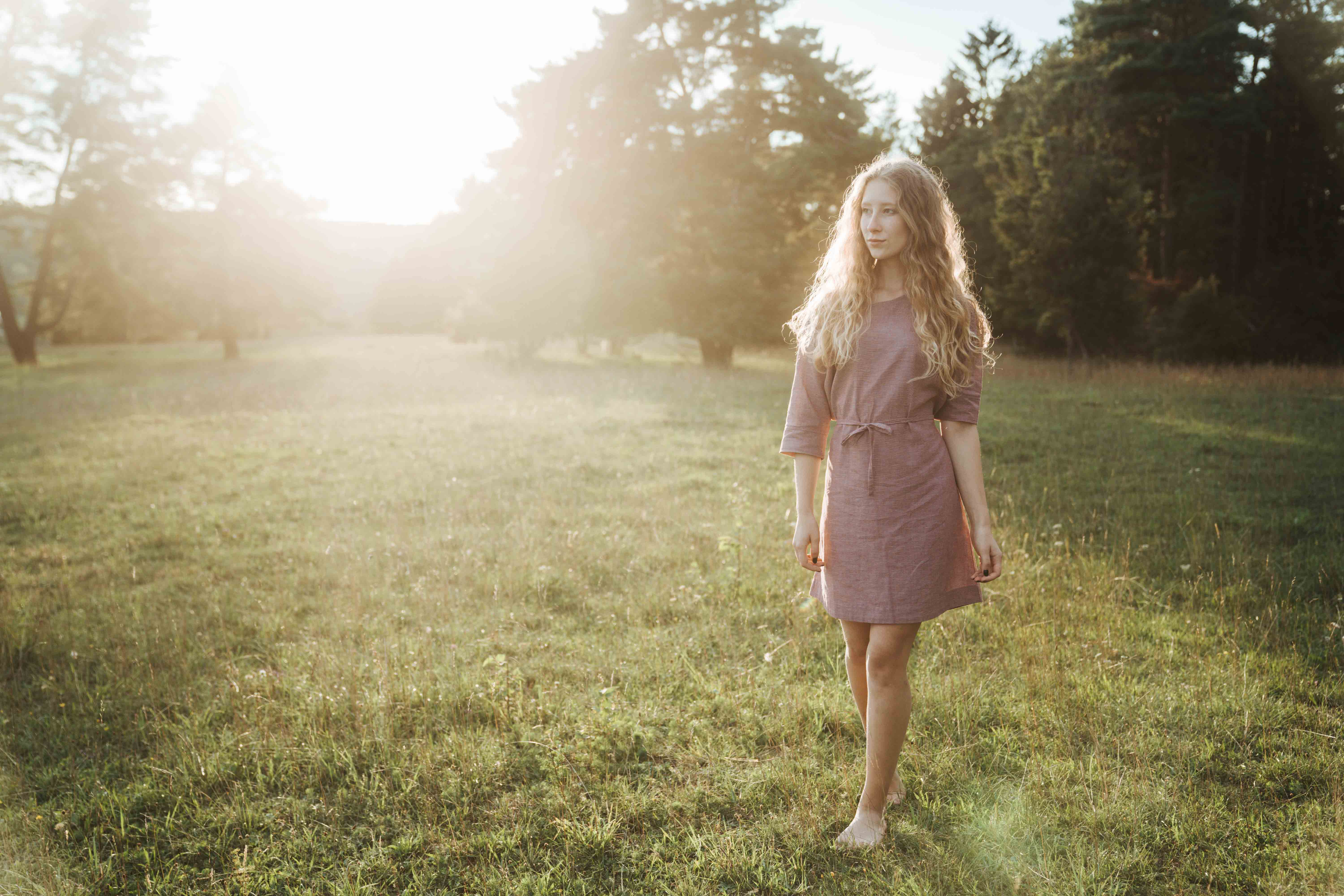 Girl in pink dress by Elkline standing in sunlight surrounded by nature