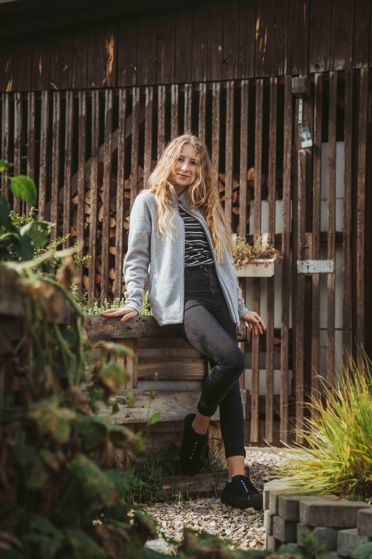 Girl standing in the Backyard wearing a grey jacket by Elkline