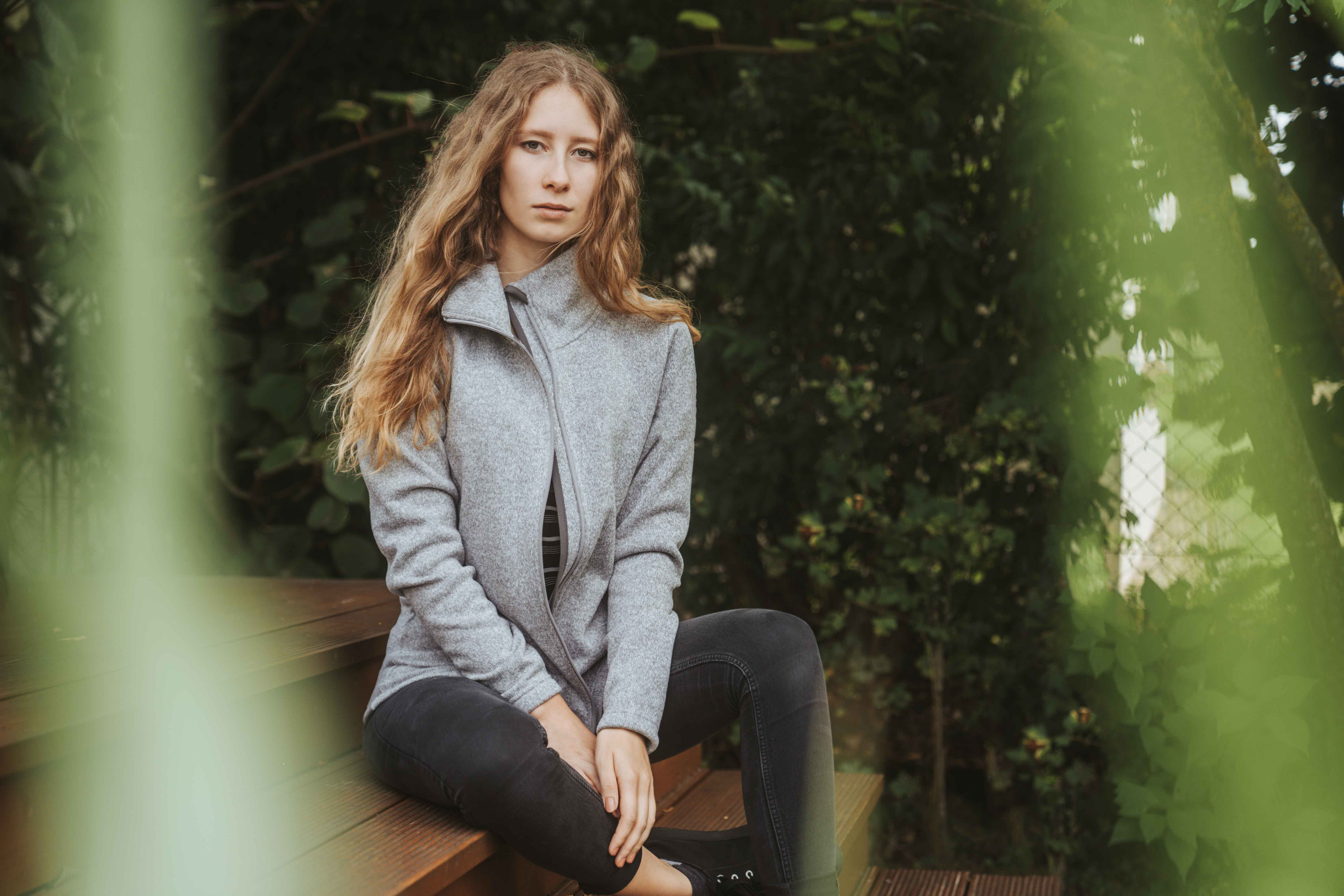 Girl sitting on stairs wearing a grey jacket by Elkline