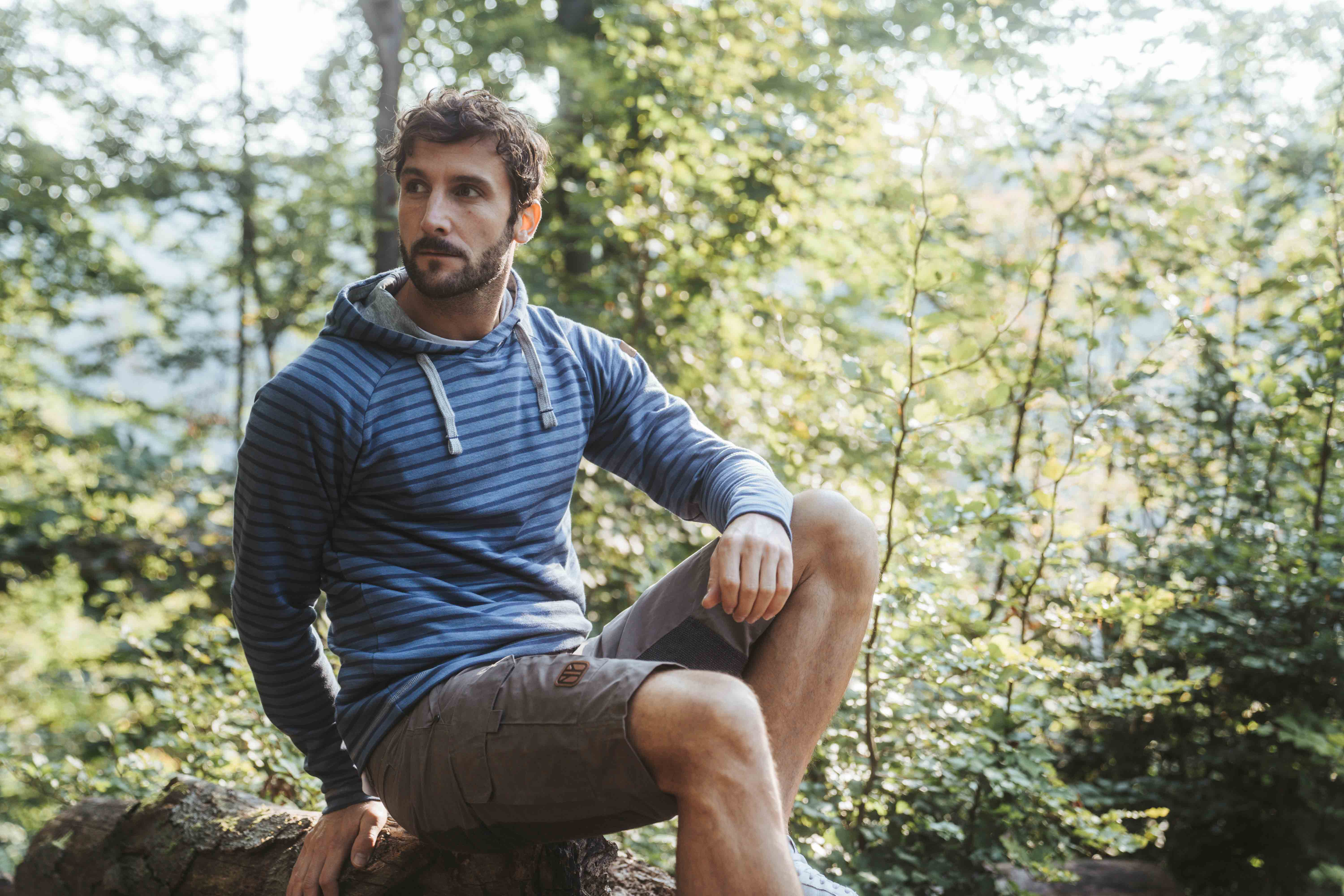 middle aged man with beard wearing blue striped sweater by Elkline sitting in nature surrounded by trees