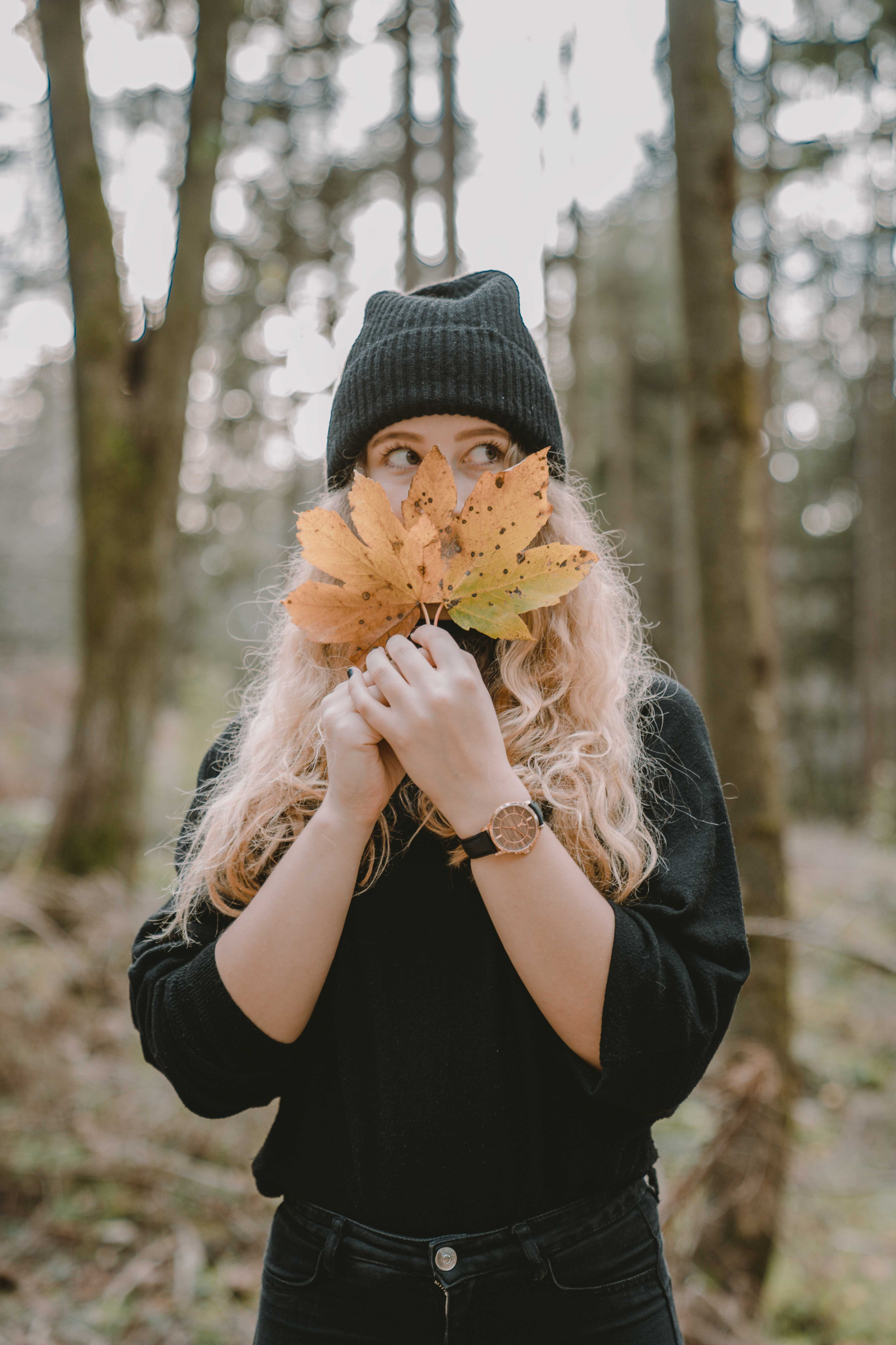 Girl hiding her face behind orange autumn leaves wearing a wrist watch by Timber&Jack