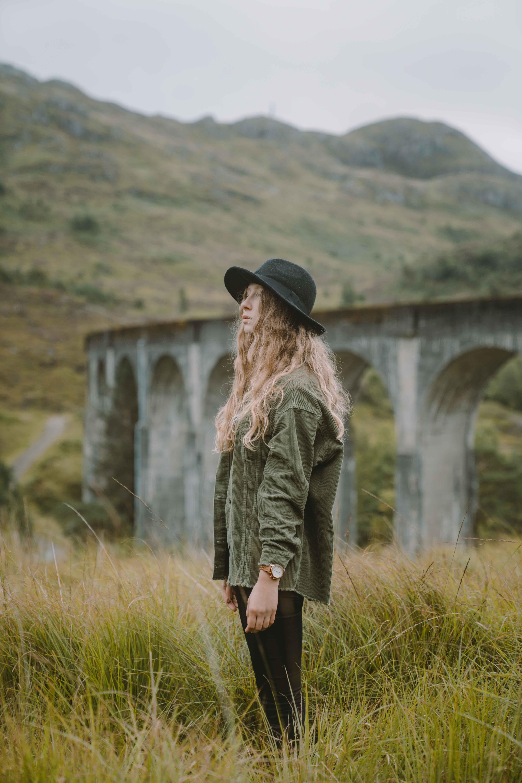 Girl standing in grass field wearing a hat