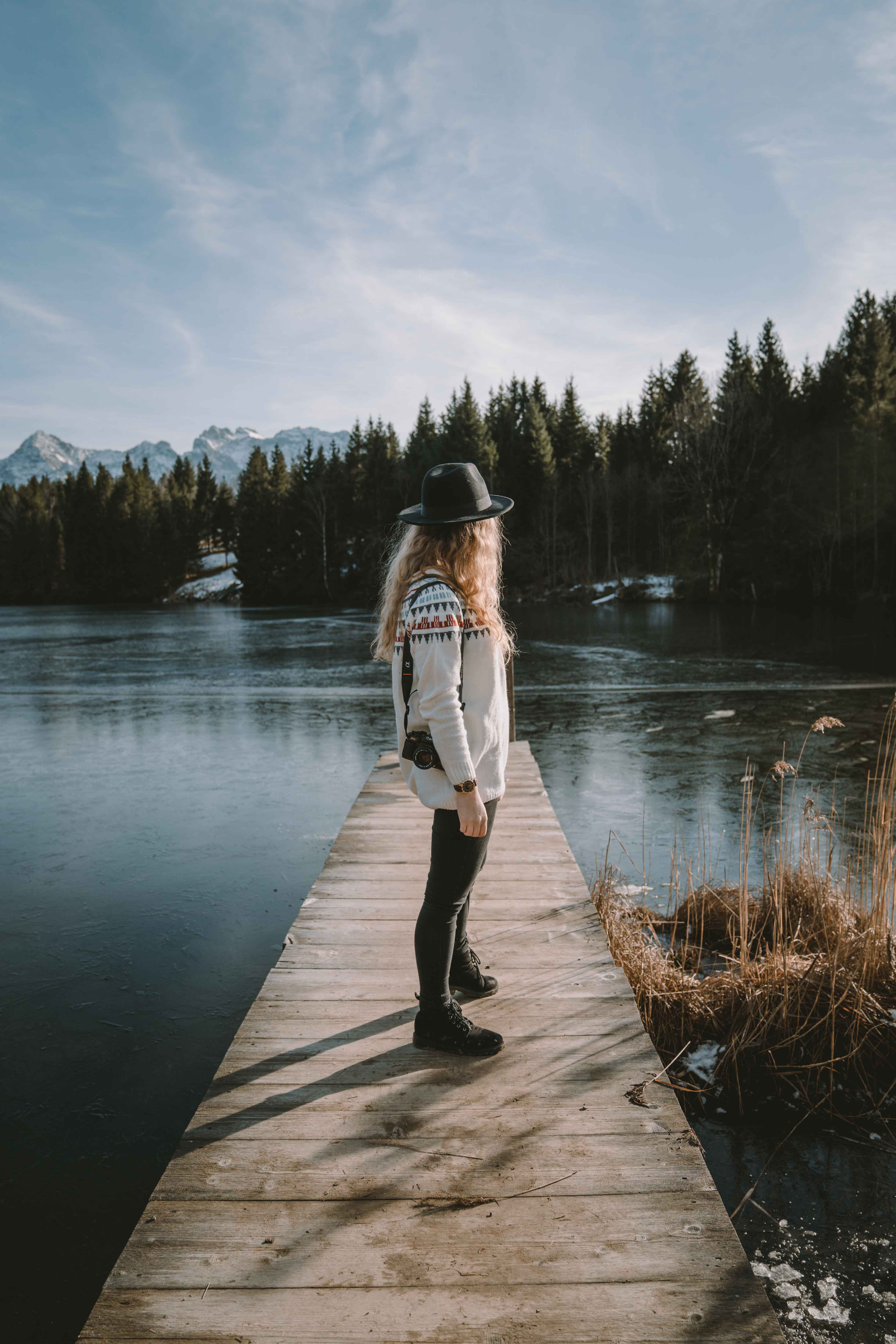 Girl standing on small pier at lake Gerold in Germany carrying a camera