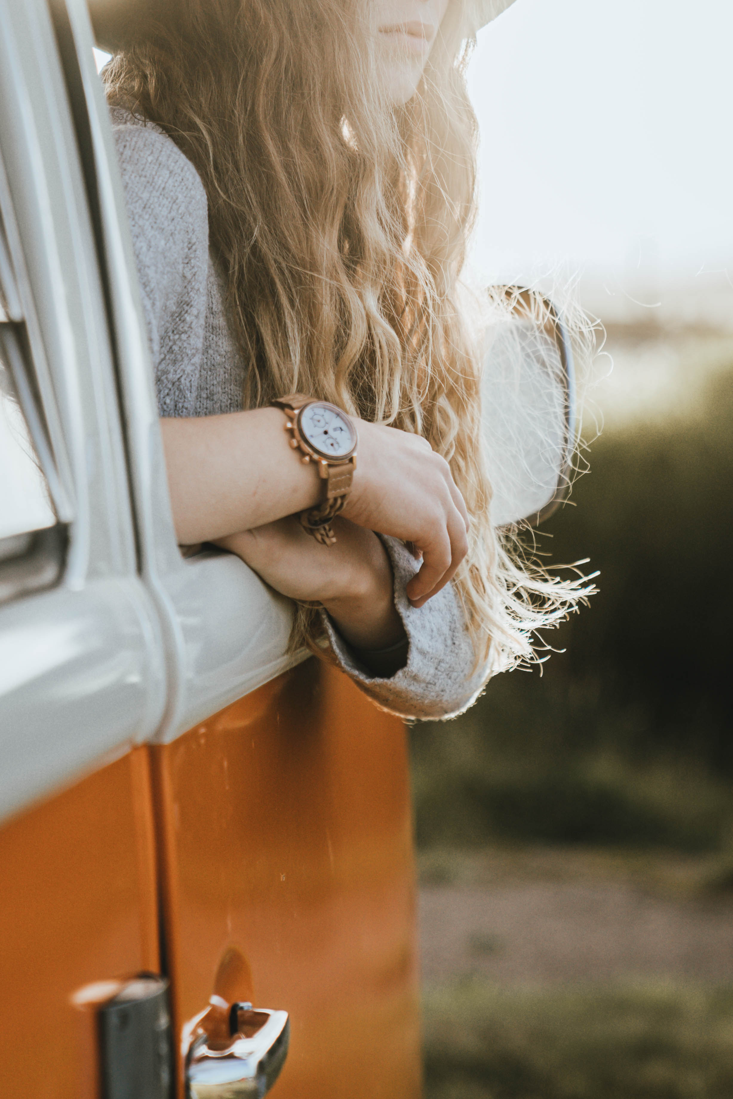 Girl leaning out of a orange van while wearing a wrist watch by Timber&Jack