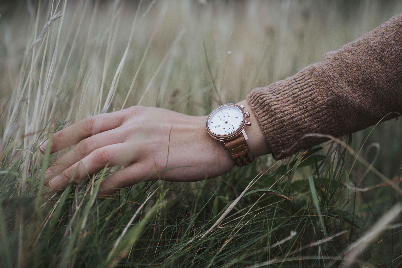Female hand touching grass wearing a Timber&Jack wrist watch