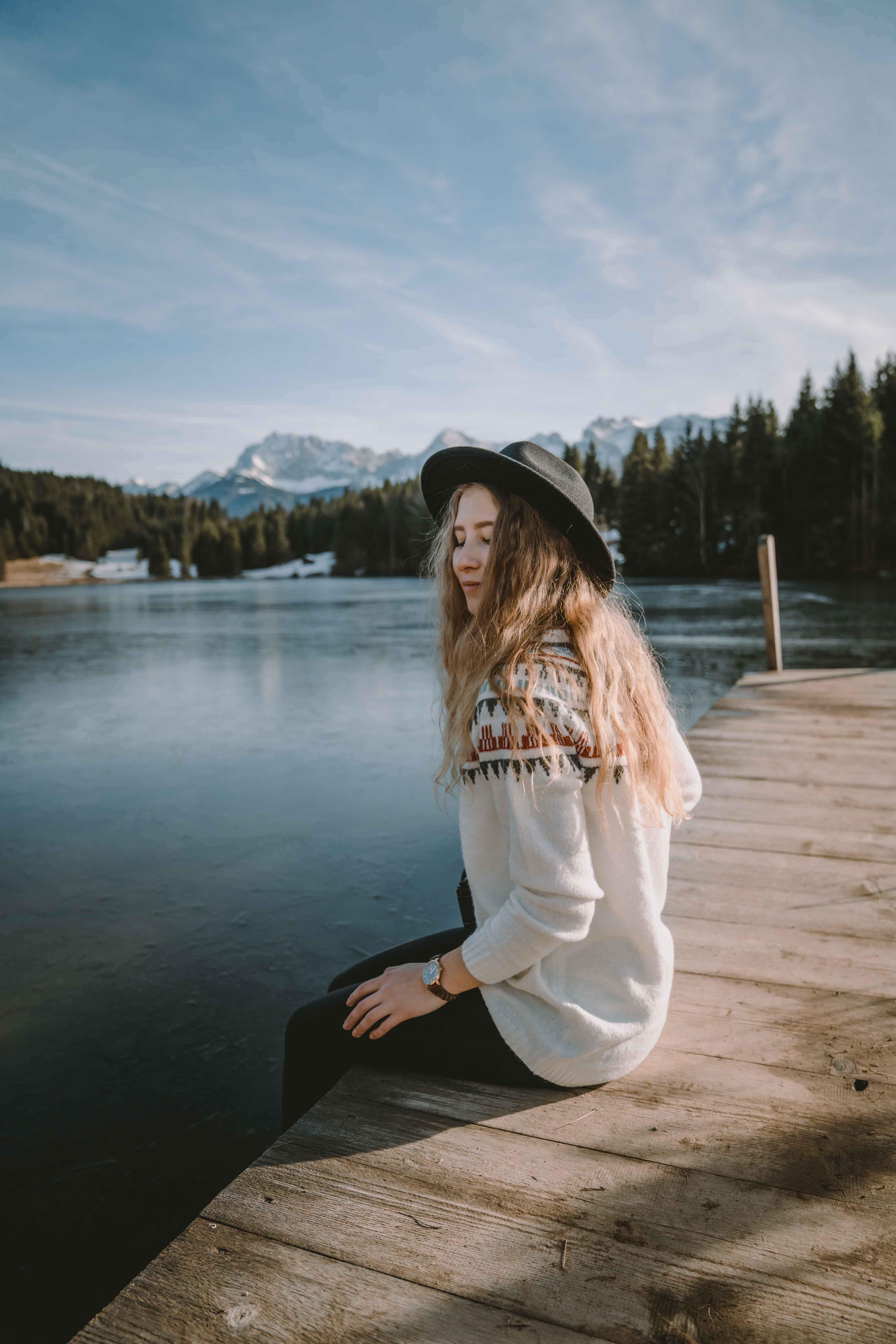 Girl sitting by the lake wearing a hat smiling
