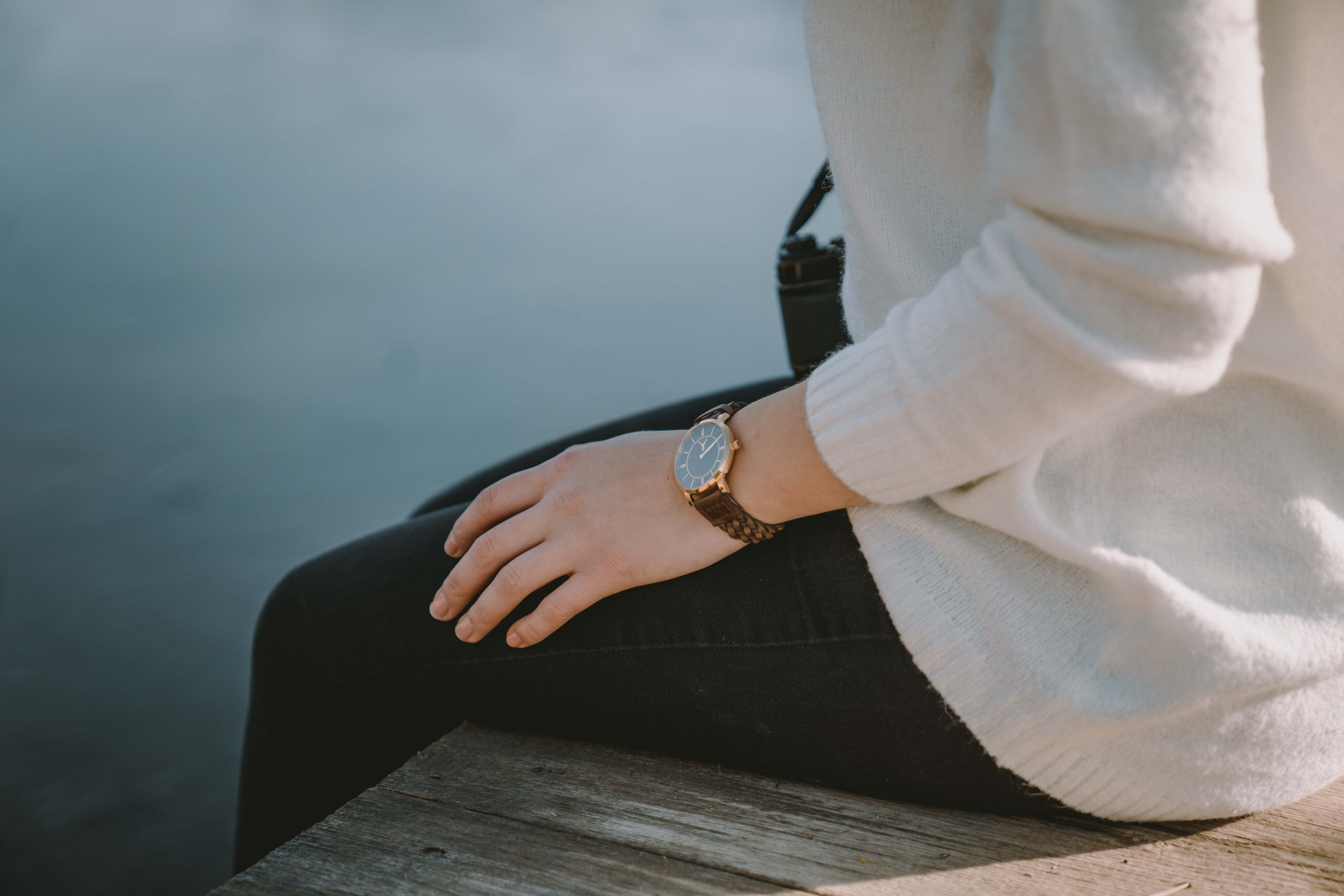 Girl sitting by the lake wearing a wrist watch by timber&jack