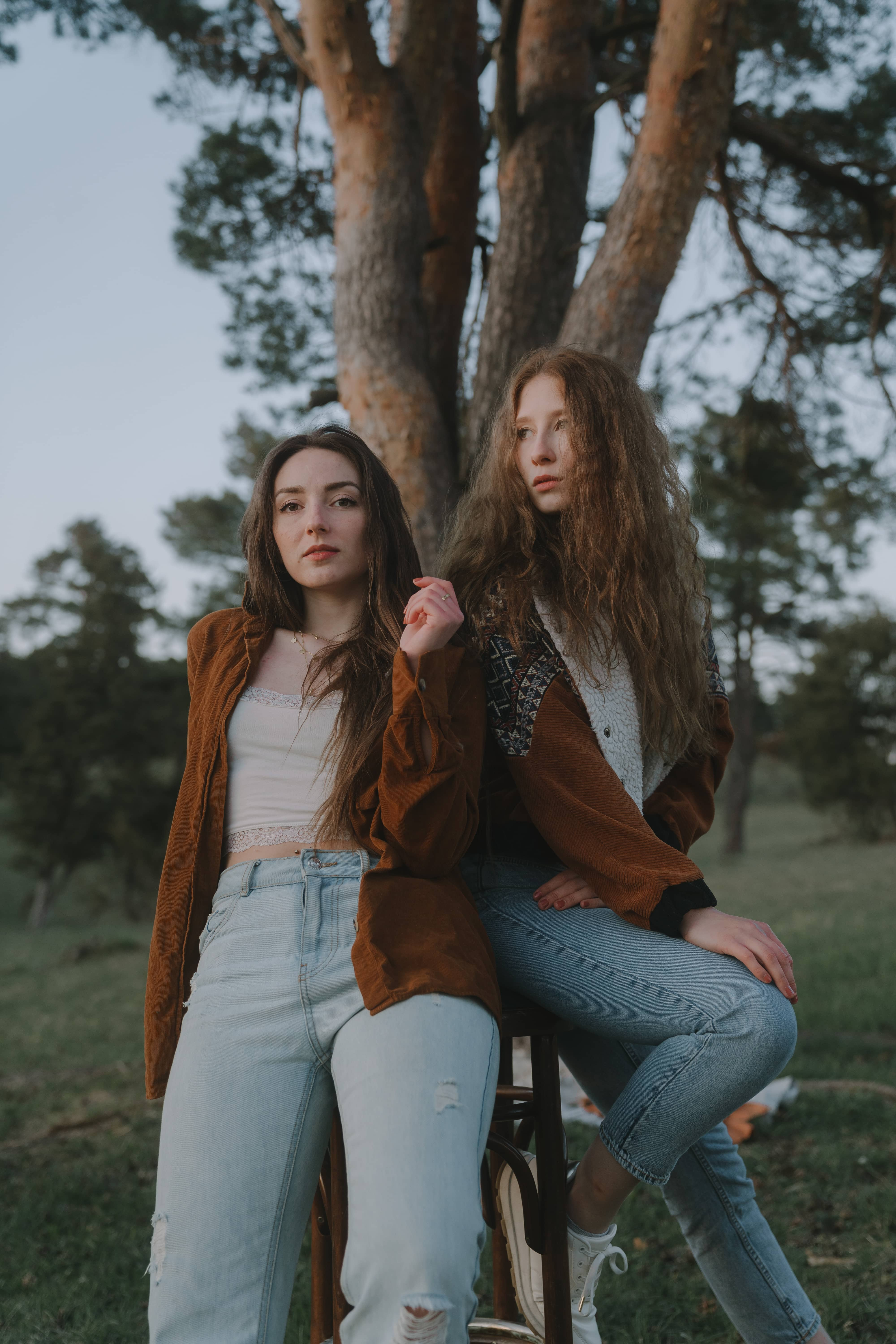 Two fashionable dressed girls leaning against each other