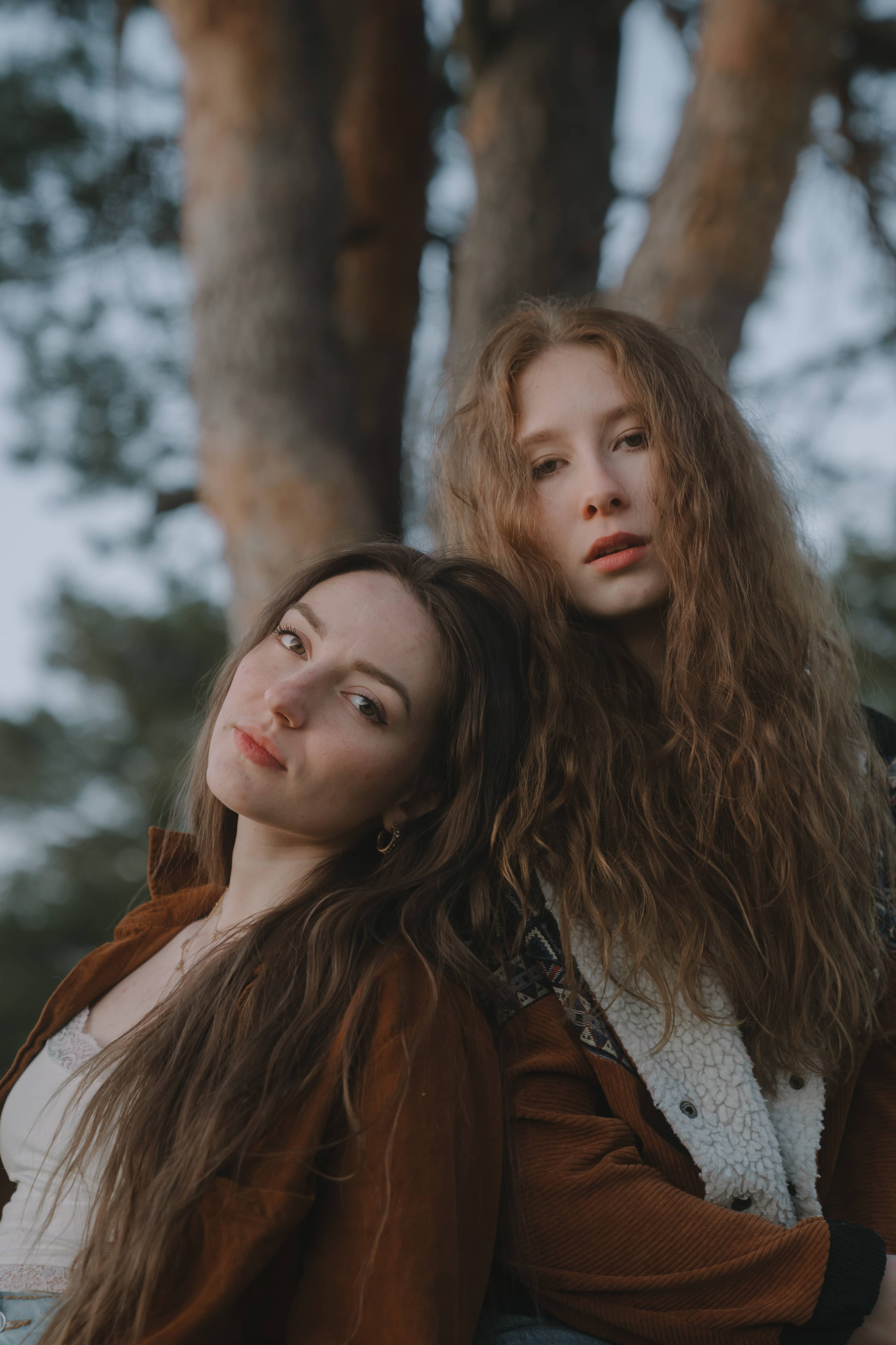 two brown haired women leaning against each other