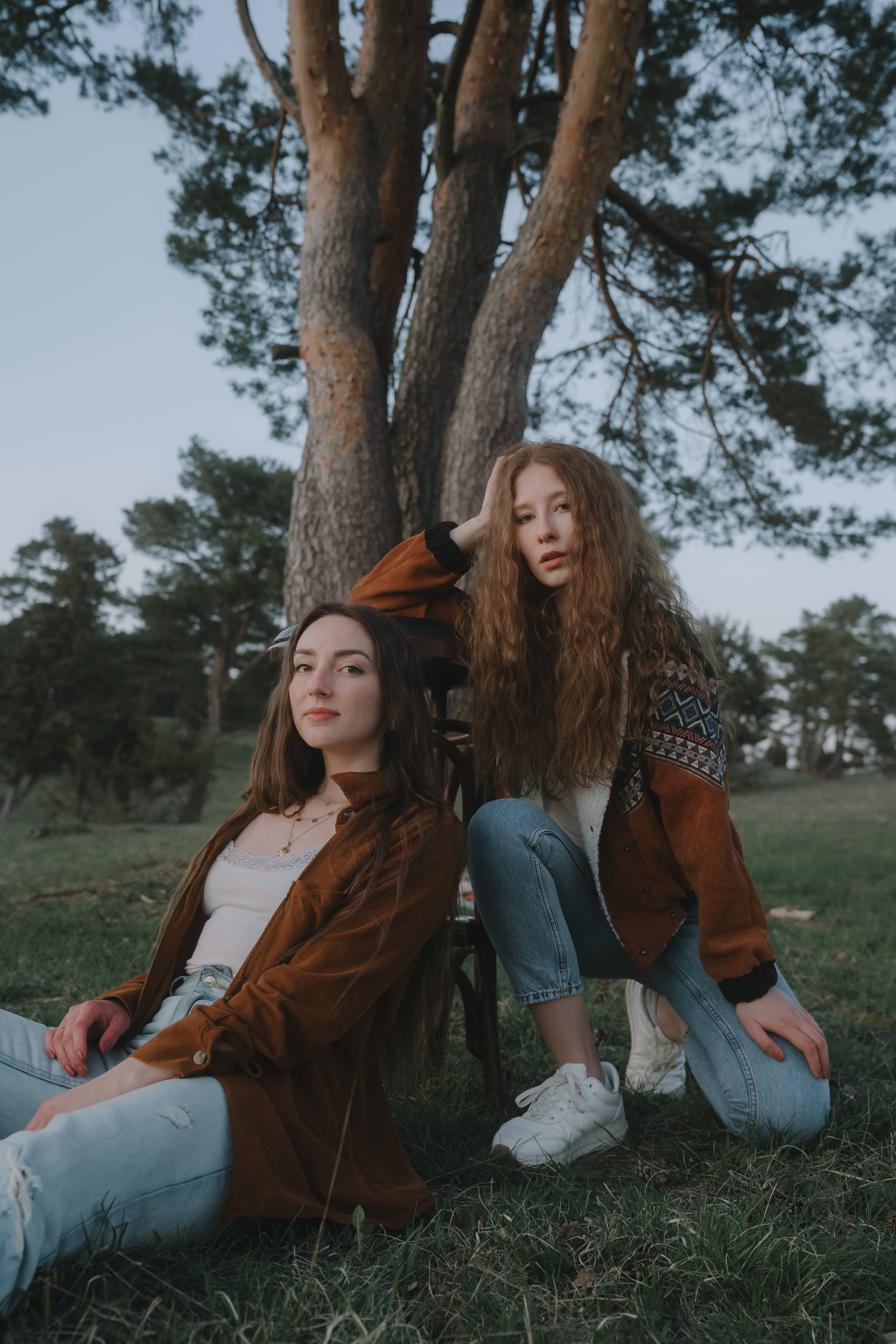 two girls fashionably dressed leaning against chair in nature