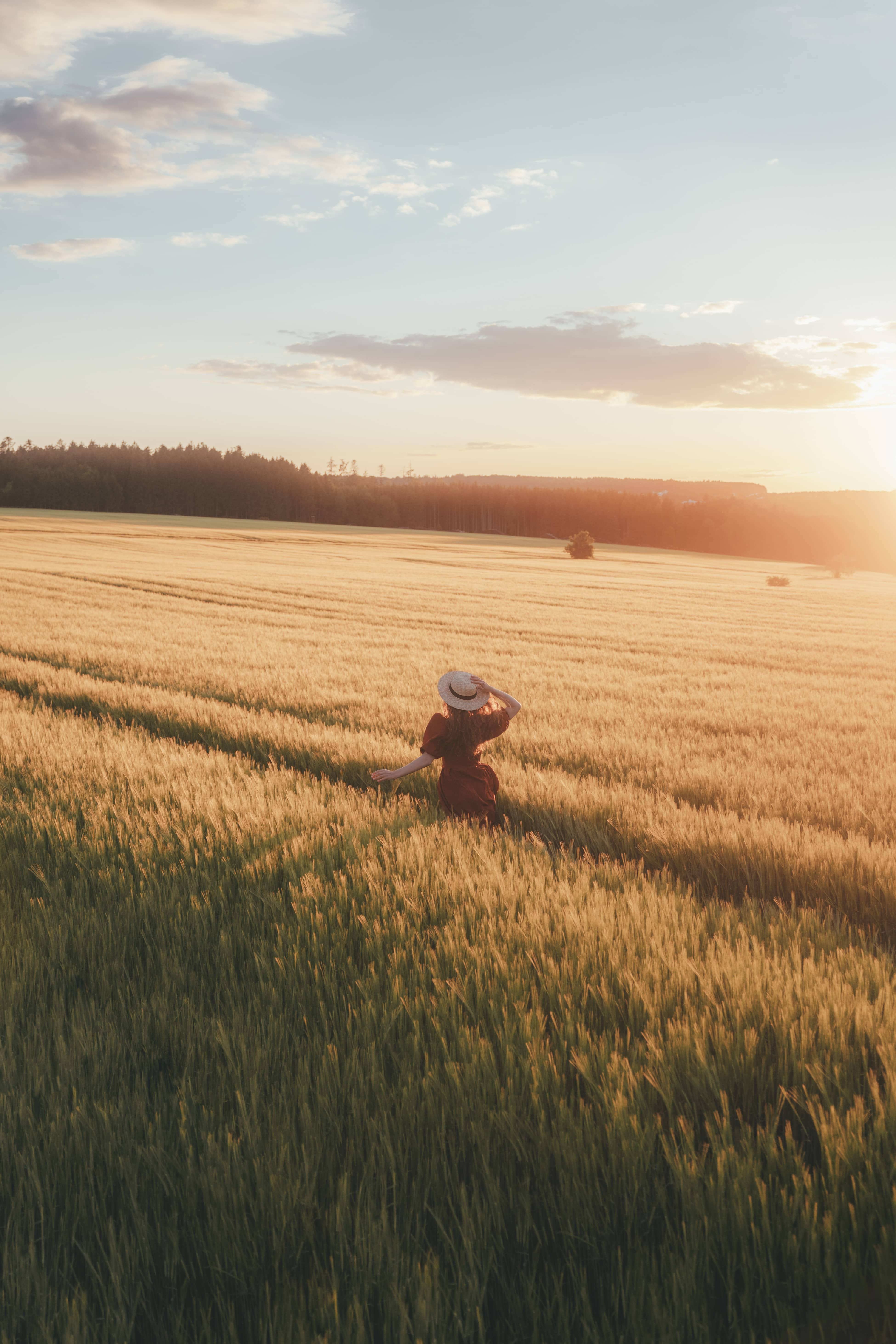 Girl in dress running through wheat field while the sun is setting in the backround