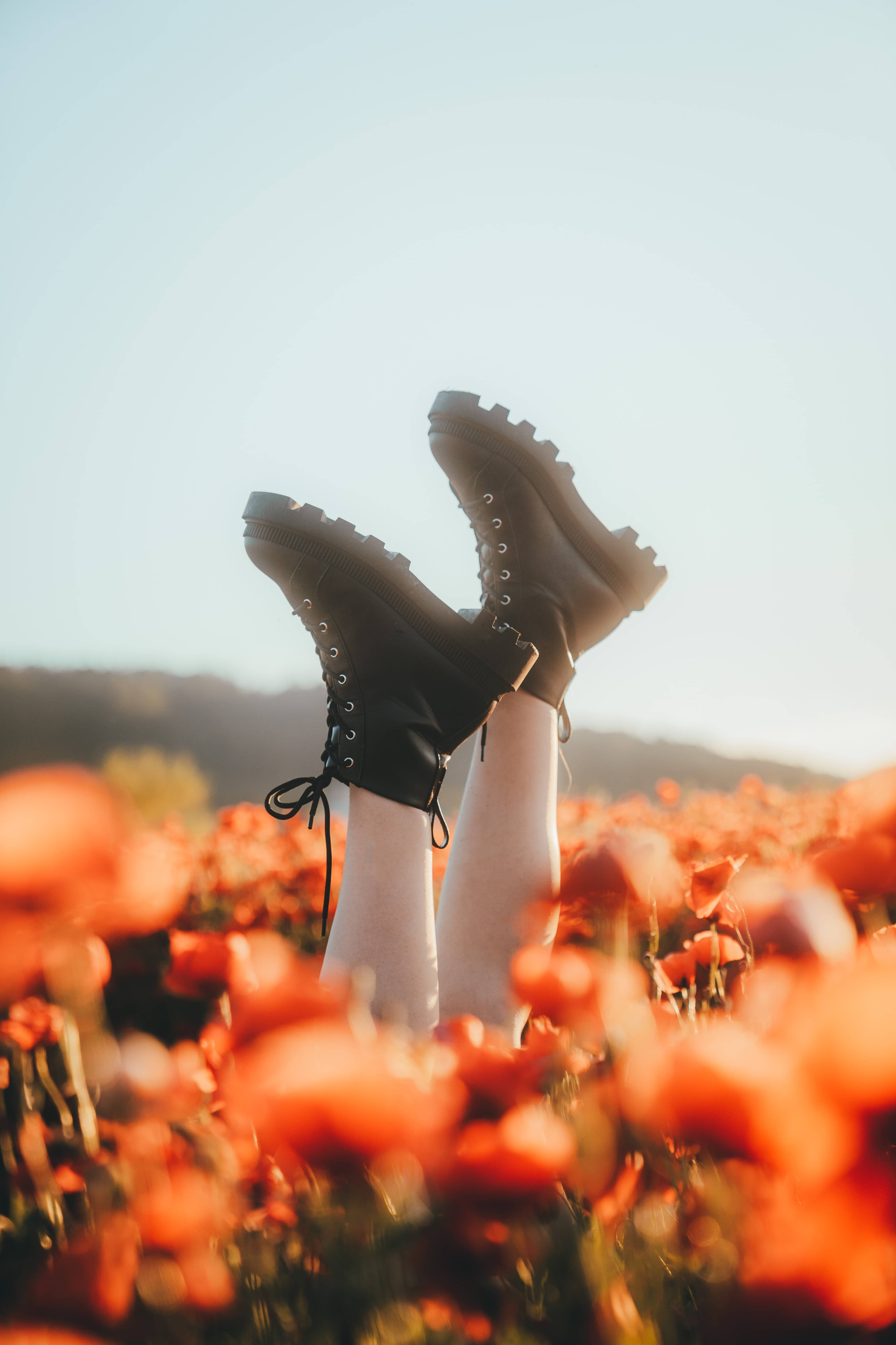 big black boots upside sown surrounded by poppy flowers