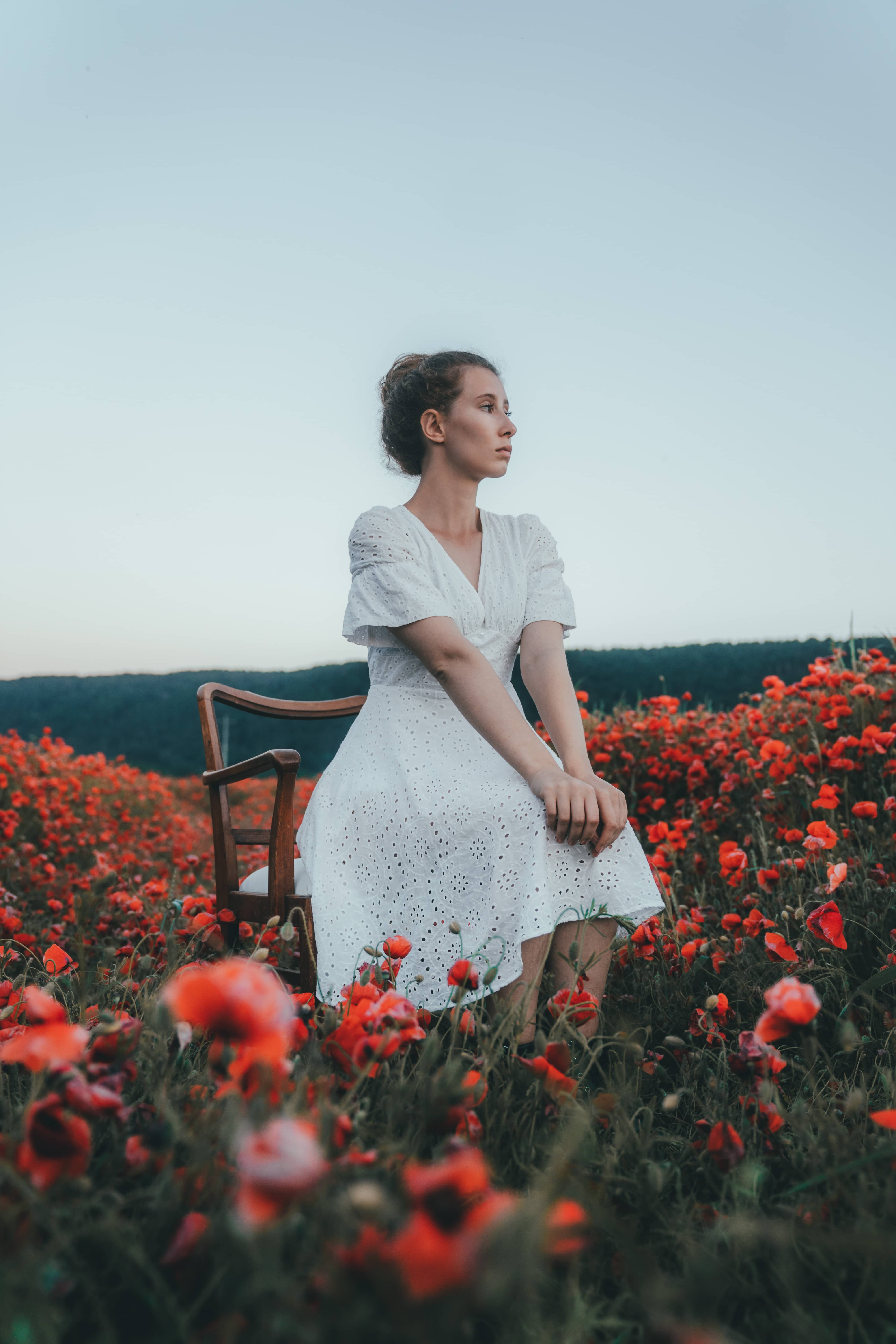 girl in white dress sitting on a chair surrounded by red poppy flowers