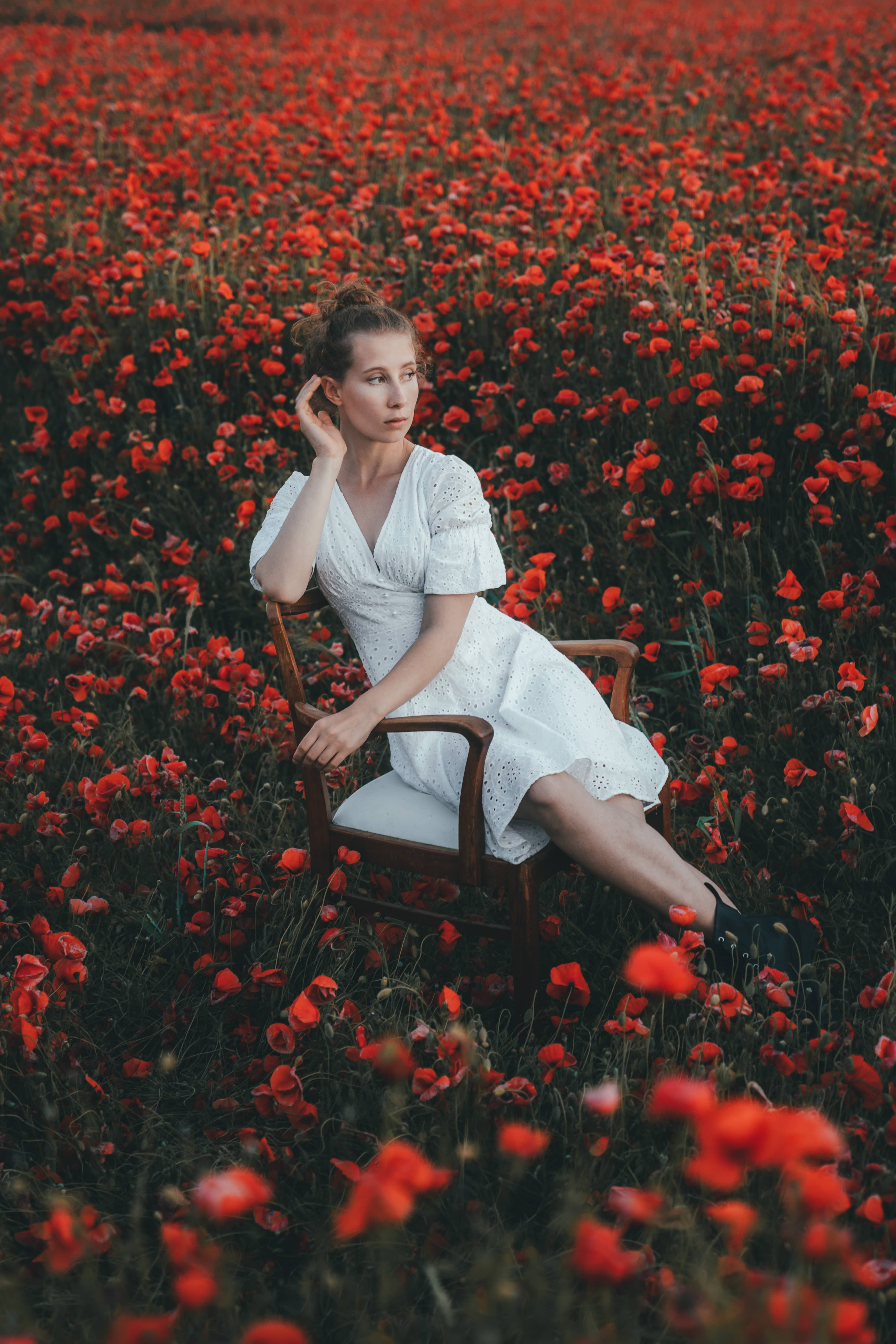 A girl in a dress sitting on a chair, being surrounded by poppy flowers