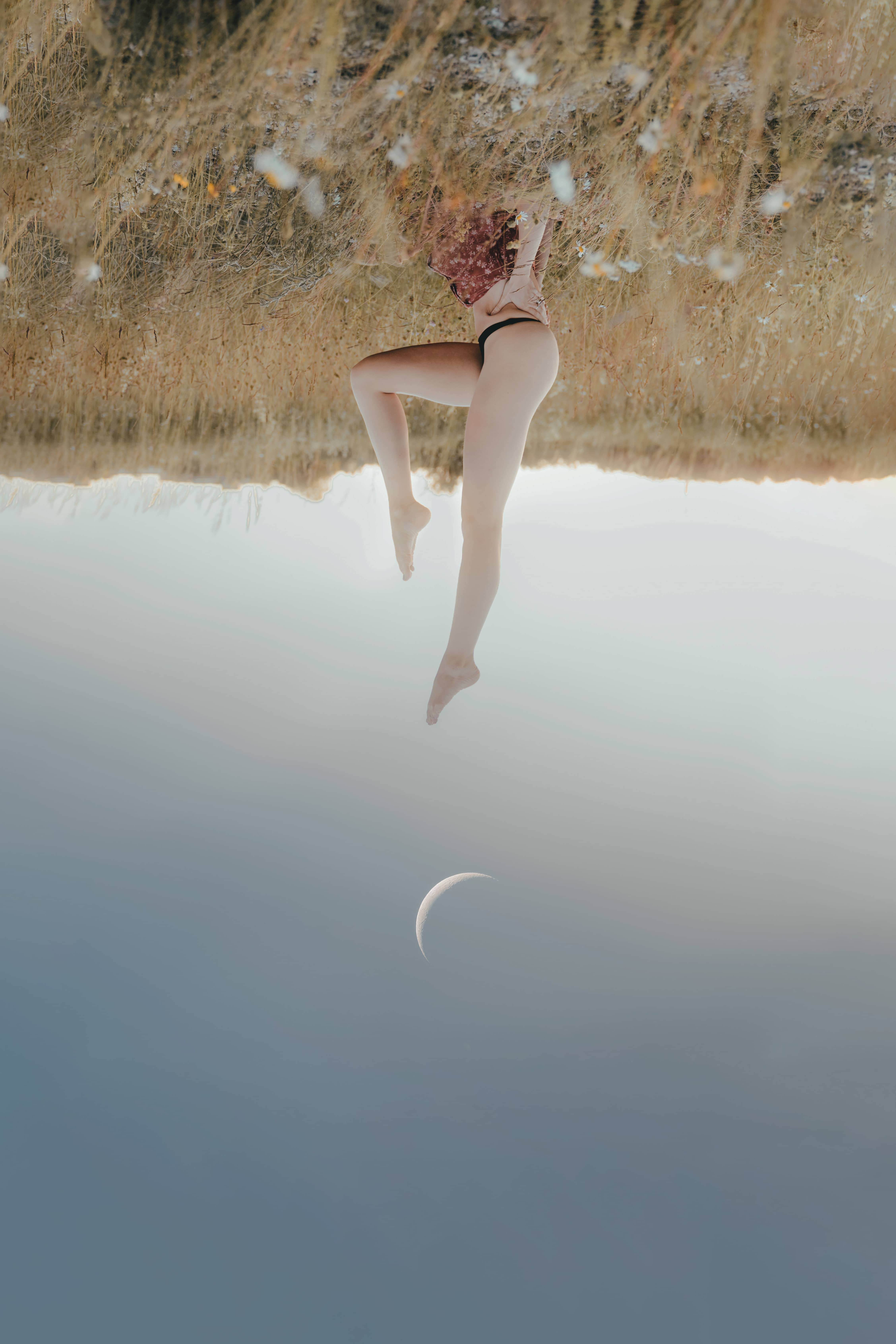 girl with no pants on laying upside down in a grass field while the half moon is rising in the background