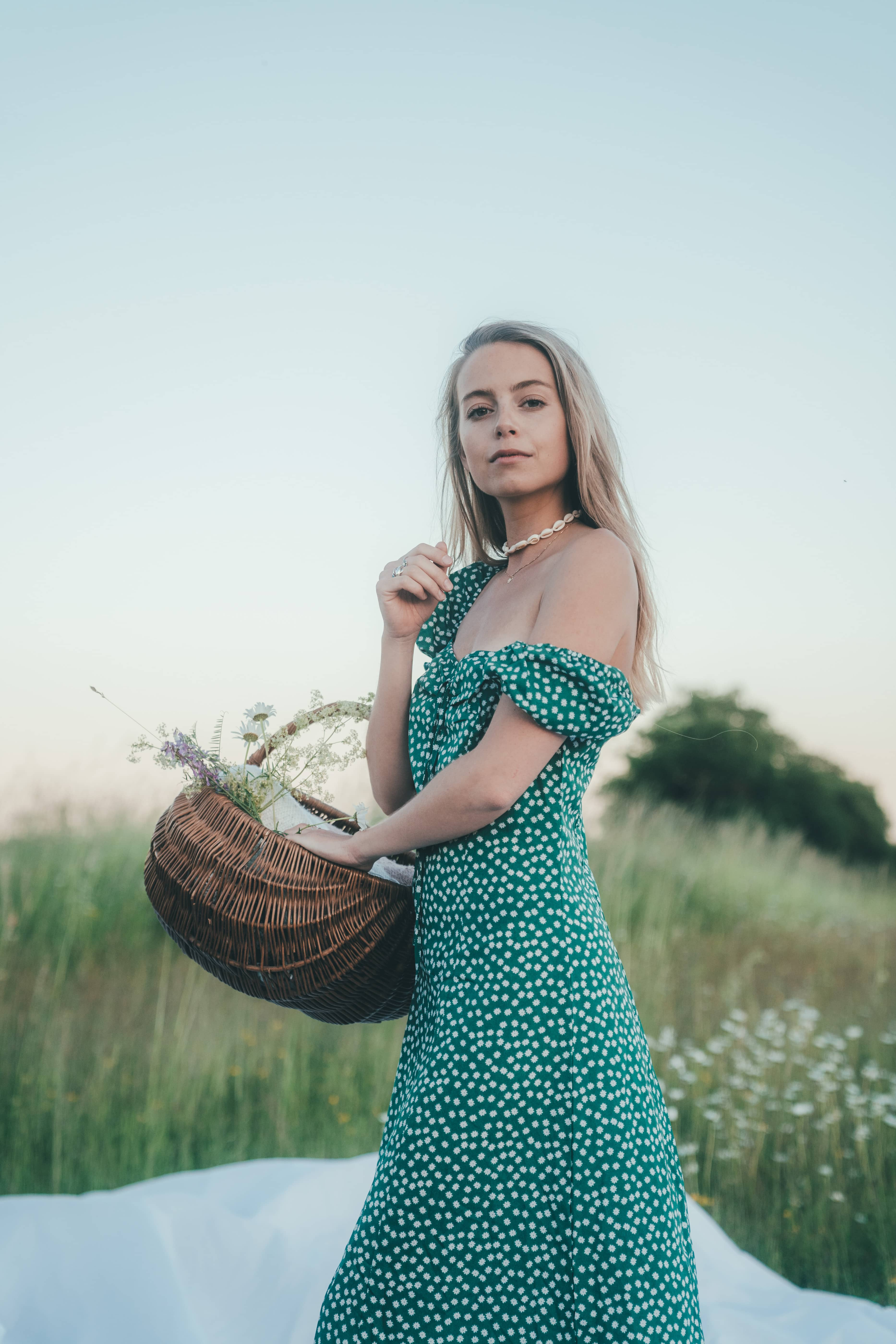 women in fashionable green dress with white dots carrying a basket dull of flowers