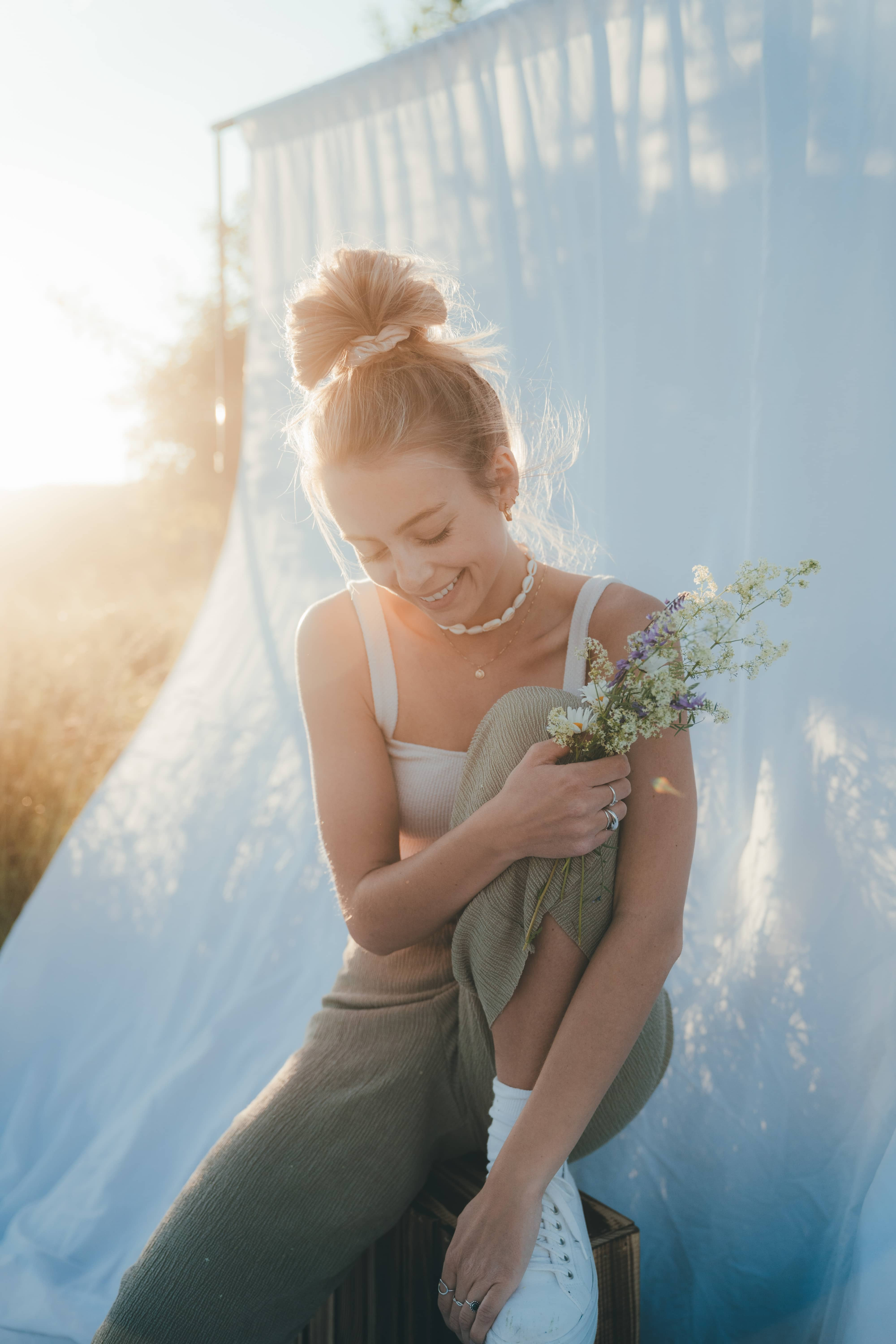 Women sitting and laughing with flowers in her hands while the sun is setting behind her