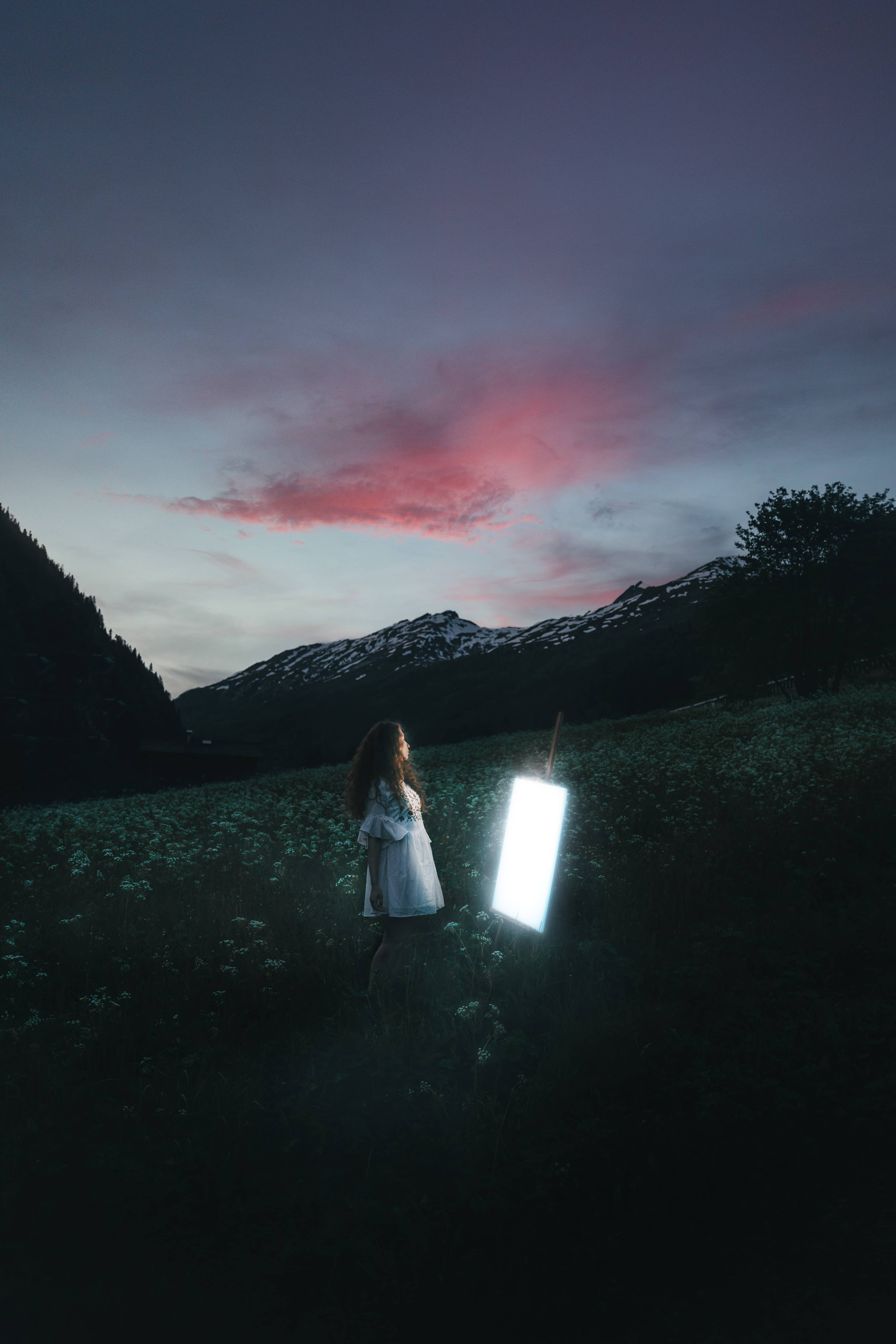 A girl standing in front of a shining screen surrounded by mountains